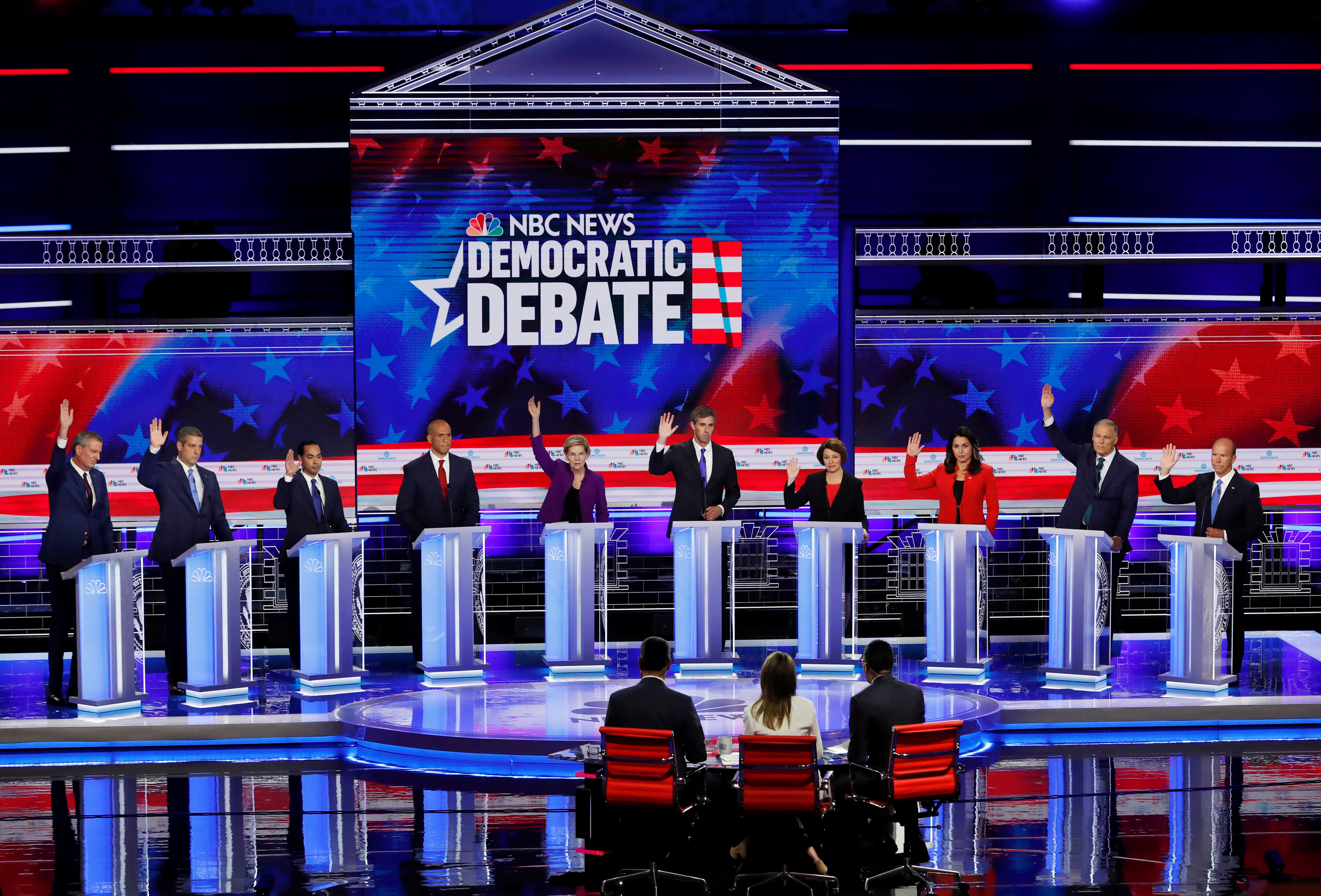 All candidates except U.S. Senator Cory Booker raise their hands while responding to a question that they would currently support the original Iran nuclear agreement during the first U.S. 2020 presidential election Democratic candidates debate in Miami, Florida, U.S., June 26, 2019. REUTERS/Mike Segar