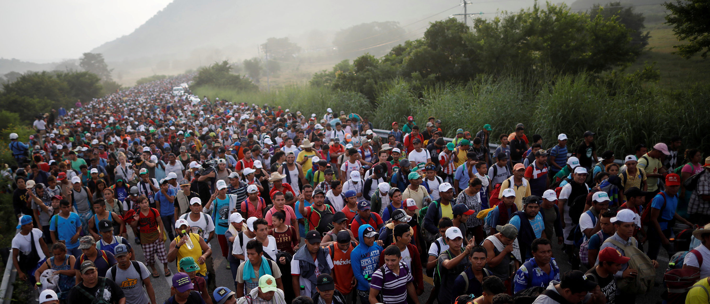 """A caravan of thousands of migrants from Central America, en route to the United States, makes its way to San Pedro Tapanatepec from Arriaga, Mexico, October 27, 2018. Reuters photographer Ueslei Marcelino: """"The caravan had gone through a tense night in Arriaga - the famous train """"La Bestia"""", which many migrants use to travel north, wasn't running which frustrated their plan to shorten their journey. They continued by road and arrived at a police blockade. The migrants moved closer together to try to protect themselves as they feared the police might take action to stop the advance of the caravan. Tense moments ensued before the police allowed the migrants to pass. When I saw a van parked at the side of the road I climbed on the roof and was astonished at how many people I could see from up above."""" REUTERS/Ueslei Marcelino."""