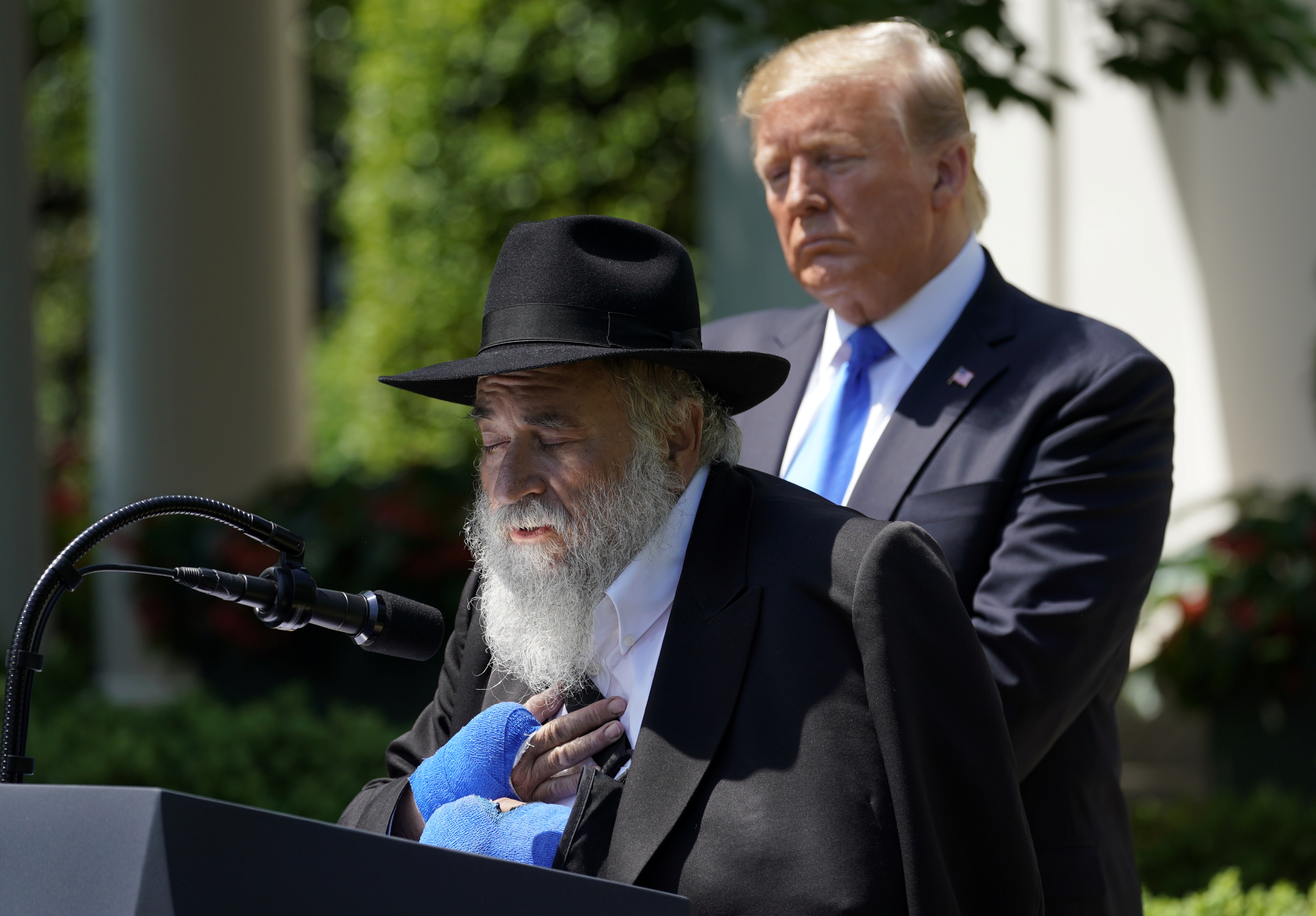 "Rabbi Yisroel Goldstein, injured in the recent shooting at the Congregation Chabad synagogue in Poway, California, speaks as U.S. President Donald Trump looks on during the ""National Day of Prayer"" Service in the Rose Garden at the White House in Washington, U.S., May 2, 2019. REUTERS/Kevin Lamarque - RC1A115FDB50"