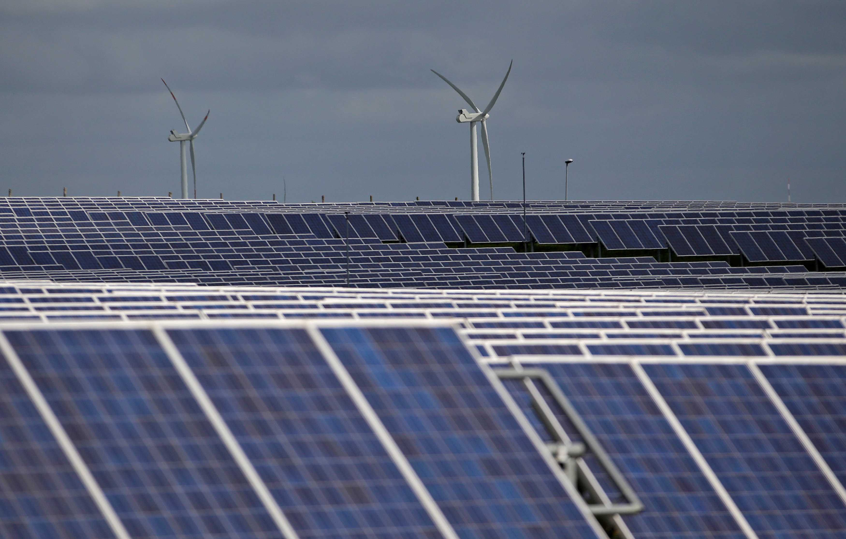 A solar power plant is seen past wind turbines in Canino
