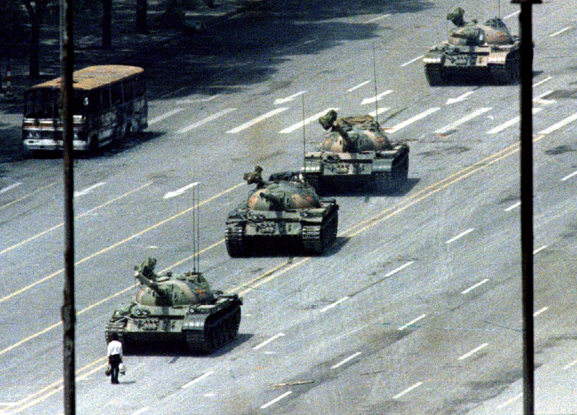 A Peking citizen stands passively in front of a convoy of tanks on the Avenue of Eternal peace. REUTERS/Stringer