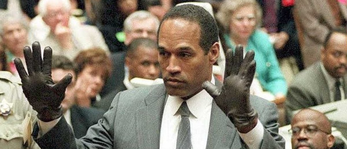 LOS ANGELES, CA - JUNE 21: O.J. Simpson shows the jury a new pair of Aris extra-large gloves, similar to the gloves found at the Bundy and Rockingham crime scene 21 June 1995, during his double murder trial in Los Angeles,CA. Deputy Sheriff Roland Jex(L) and Prosecutor Christopher Darden (R) look on. (Photo credit: VINCE BUCCI/AFP/Getty Images)
