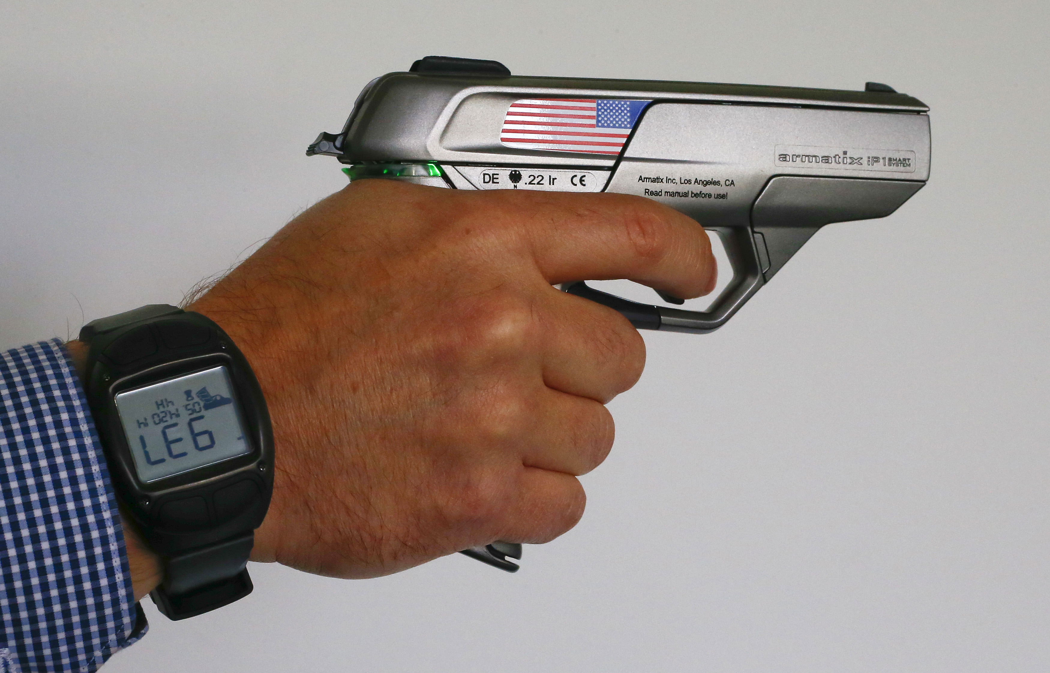 """An Armatix employee holds a smart gun by the company at the Armatix headquarters in Munich May 14, 2014. The gun is implanted with an electronic chip that allows it to be fired only if the shooter is wearing a watch that communicates with it through a radio signal. If the gun is moved more than 10 inches (25 cm) from the watch, it will not fire. A Maryland gun shop owner has dropped his plan to be the first in the United States to sell the so-called """"smart gun"""" after a backlash that included death threats. REUTERS/Michael Dalder"""
