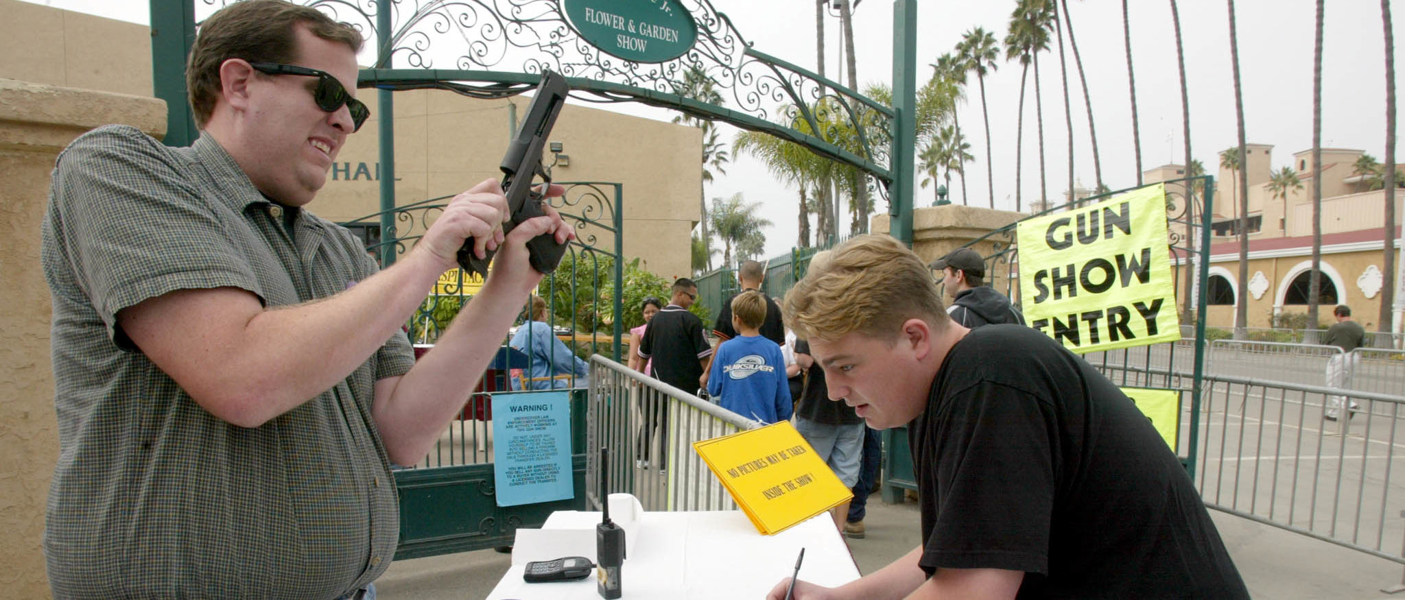 A man checks a handgun at the reception desk of the Crossroads of the West Gun Show in Del Mar, California, 20 October, 2002, where loade guns are not allowed. The show is being held several times a year in dozens of cities in the West Coast and gathers a variety of customers from law enforcement agents, military personnel, hunters and civilians to purchase weapons, ammunition, collectible items, antiques and memorabilia. (Photo by HECTOR MATA/AFP/Getty Images)