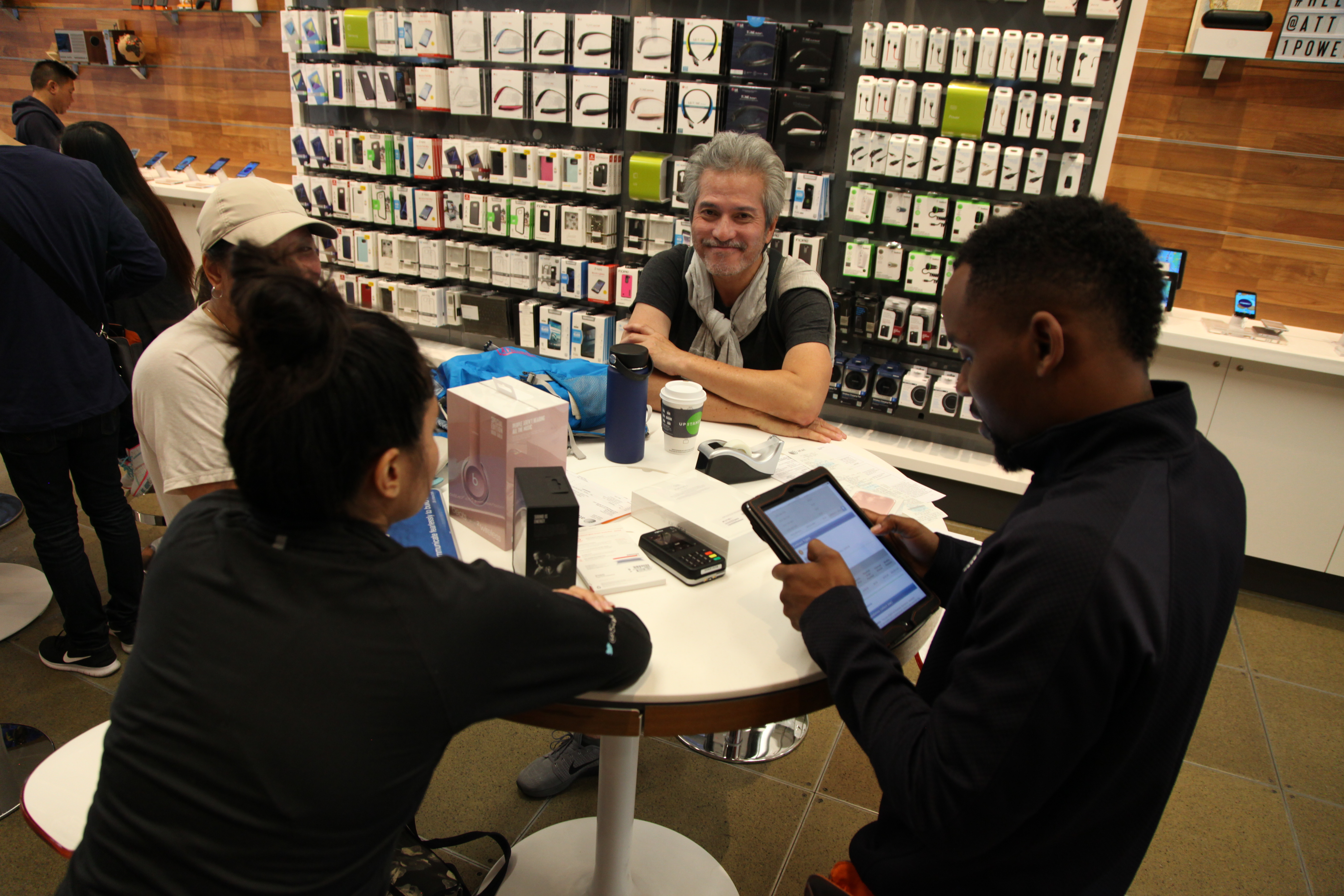 SAN FRANCISCO, CA - OCTOBER 07: An AT&T employee helps a customer set up her new device at the Grand Opening of the AT&T store at 1 Powell on October 7, 2016 in San Francisco, California. (Photo by Kelly Sullivan/Getty Images for MAC Presents)