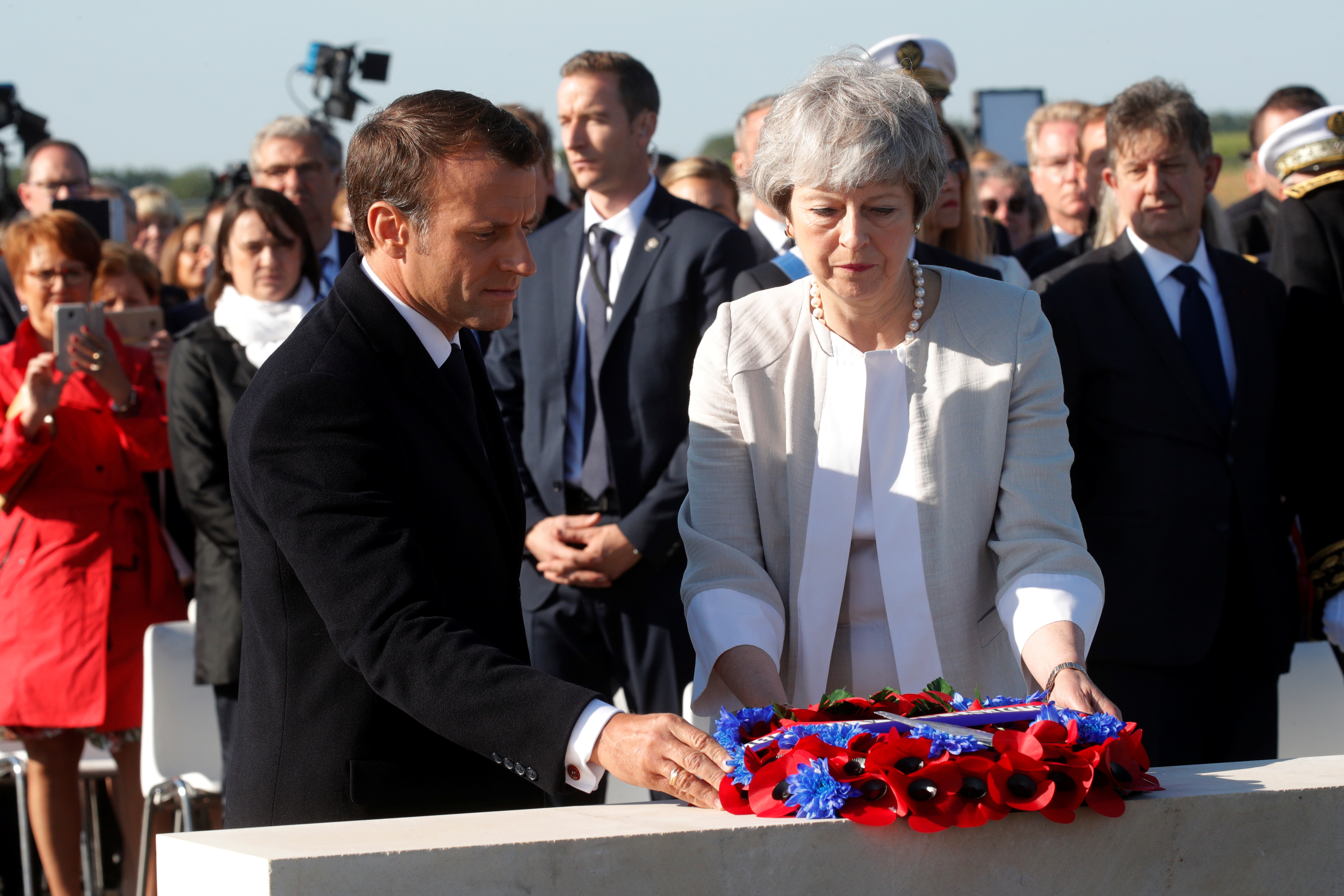 French President Emmanuel Macron and British Prime Minister Theresa May lay a wreath of flowers at the commemorative first stone of a British memorial during a Franco-British ceremony in Ver-Sur-Mer as part of ceremonies to mark the 75th anniversary of D-Day landings in Normandy, France, June 6, 2019. REUTERS/Philippe Wojazer/Pool