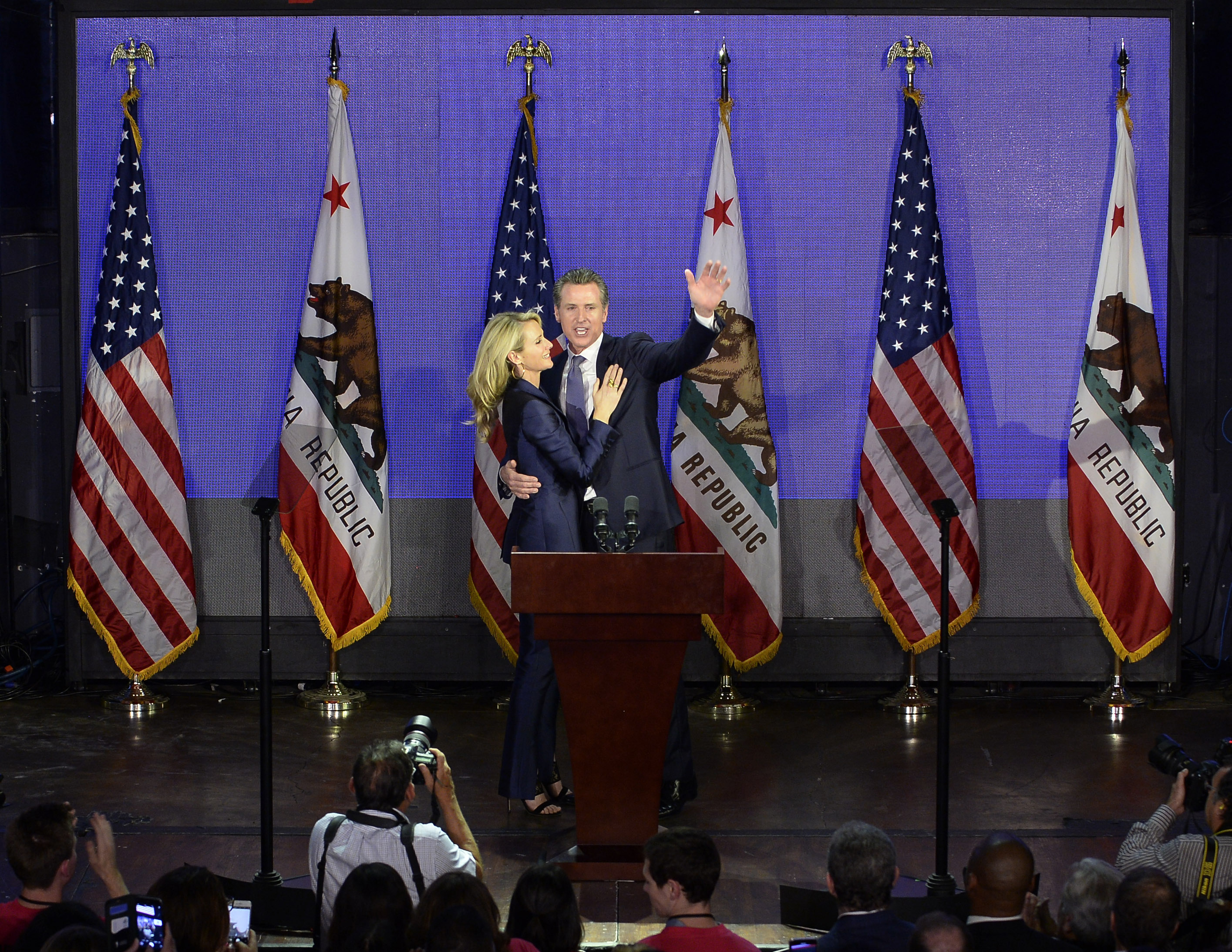 Democratic gubernatorial candidate Gavin Newsom and his wife Jennifer Siebel Newsom wave to supporters during election night event. (Kevork Djansezian/Getty Images)