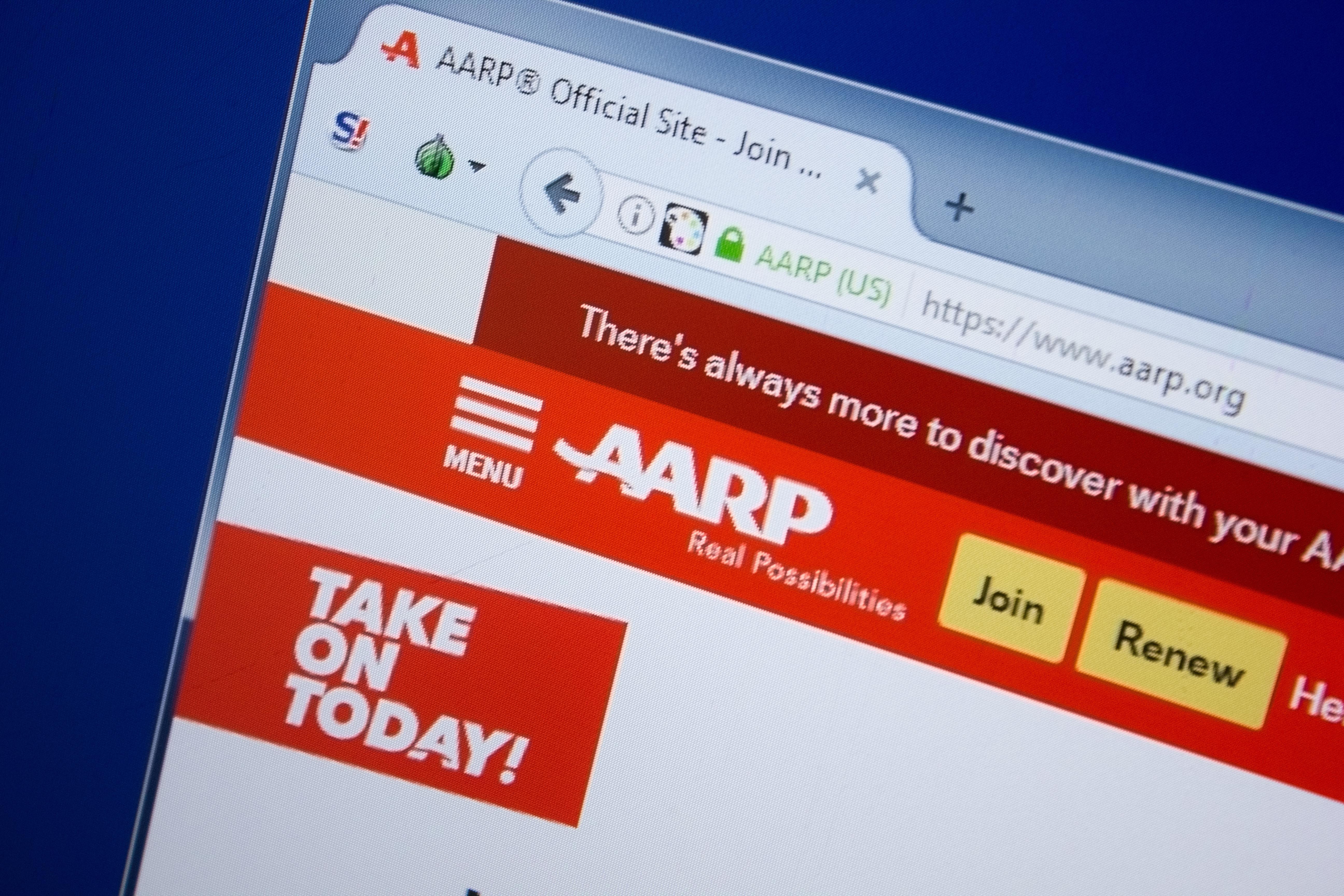 A screen displays the AARP webpage. Shutterstock image via Sharaf Maksumov