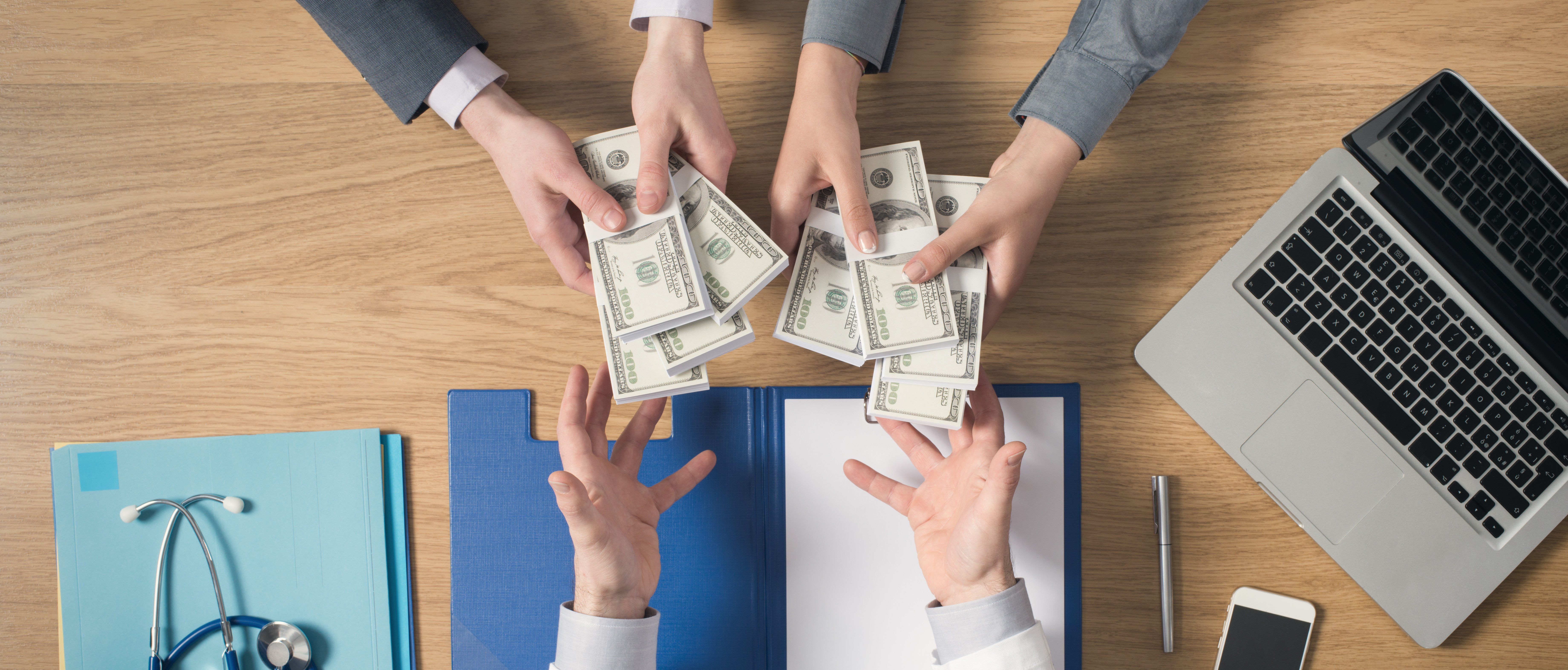 Money passes into a doctor's hands. Shutterstock image via Stokkete