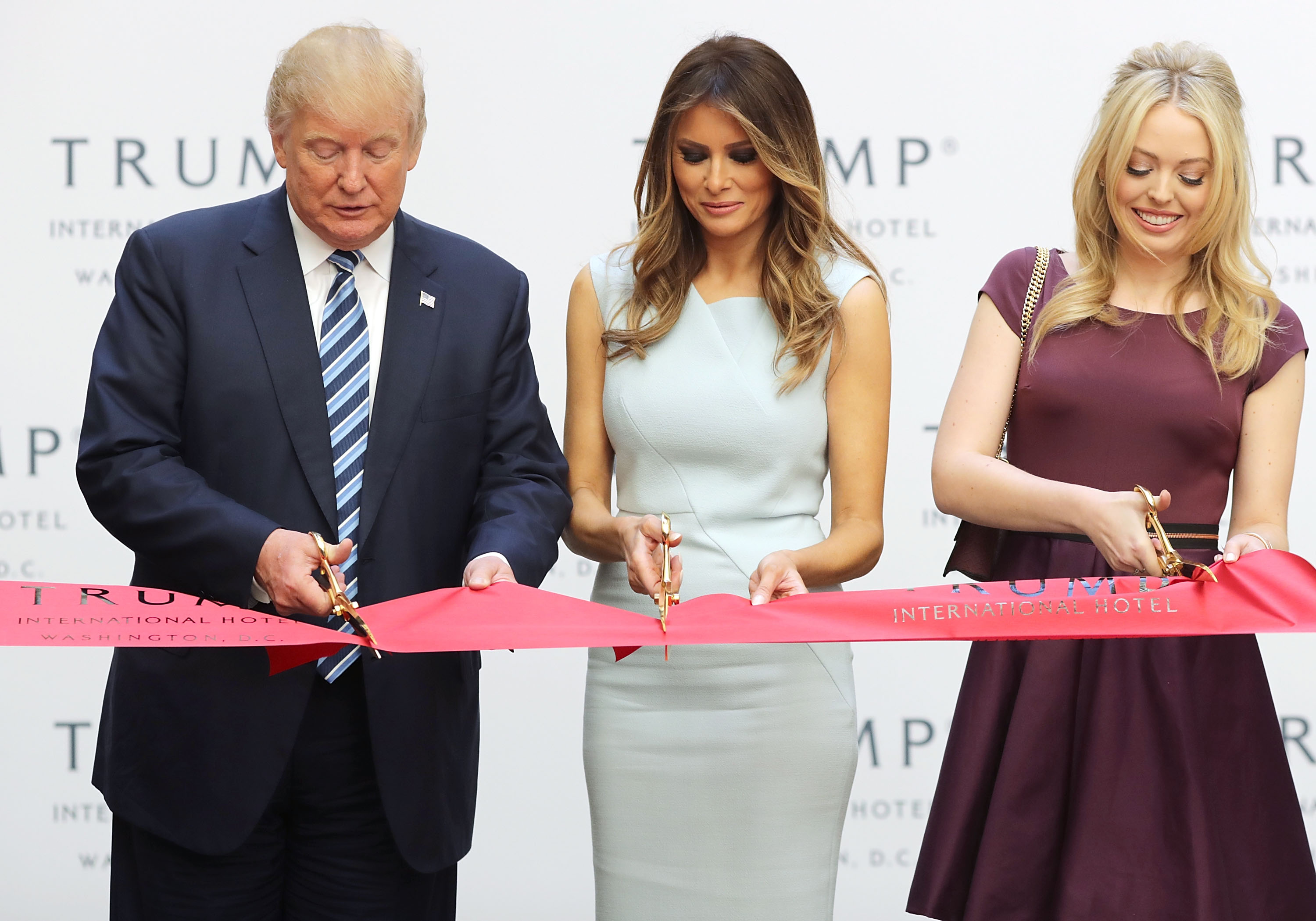 Republican presidential nominee Donald Trump, his wife Melania Trump and daughter Tiffany Trump cut the ribbon at the new Trump International Hotel October 26, 2016 in Washington, DC. (Chip Somodevilla/Getty Images)