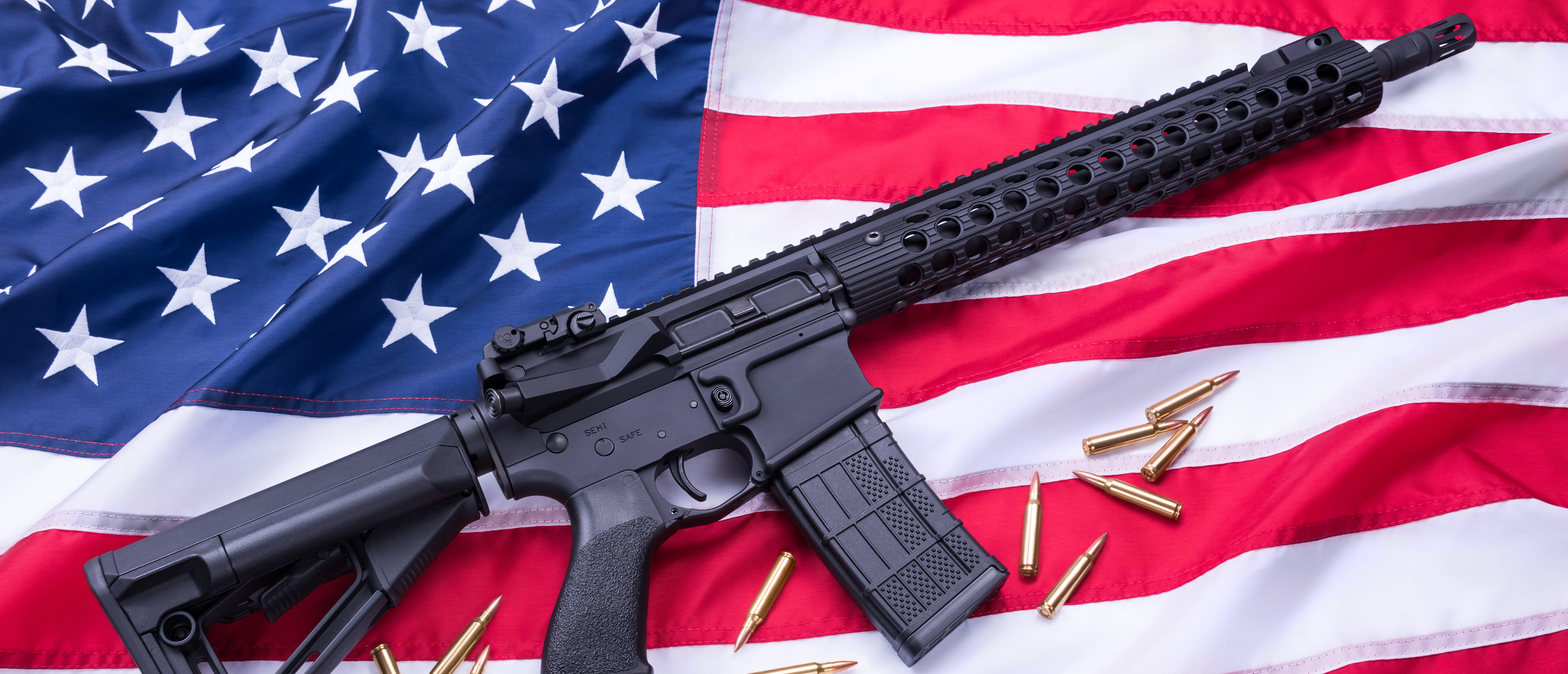 AR-15 sitting on an American flag with 5.56 caliber ammunition (Shutterstock)