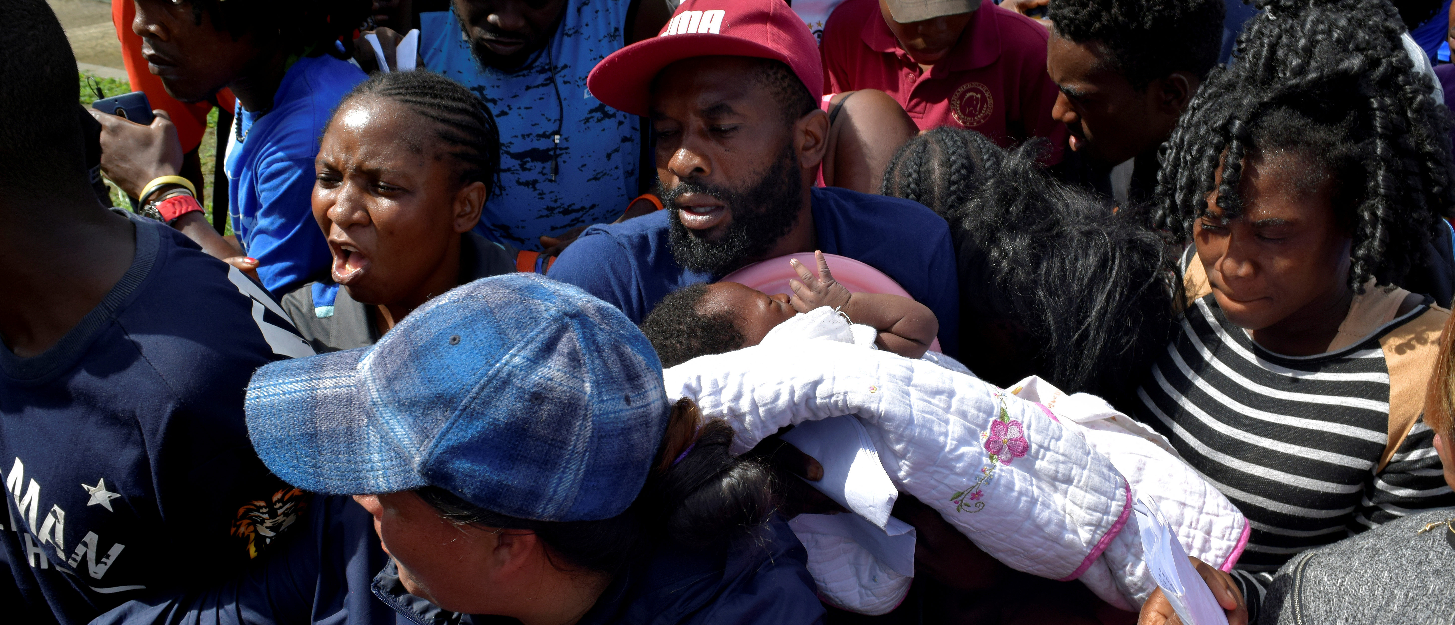 FILE PHOTO: A migrant from Cameroon holds his baby while trying to enter the Siglo XXI immigrant detention center to request humanitarian visas, issued by the Mexican government, to cross the country towards the United States, in Tapachula, Mexico June 27, 2019. REUTERS/Jose Torres