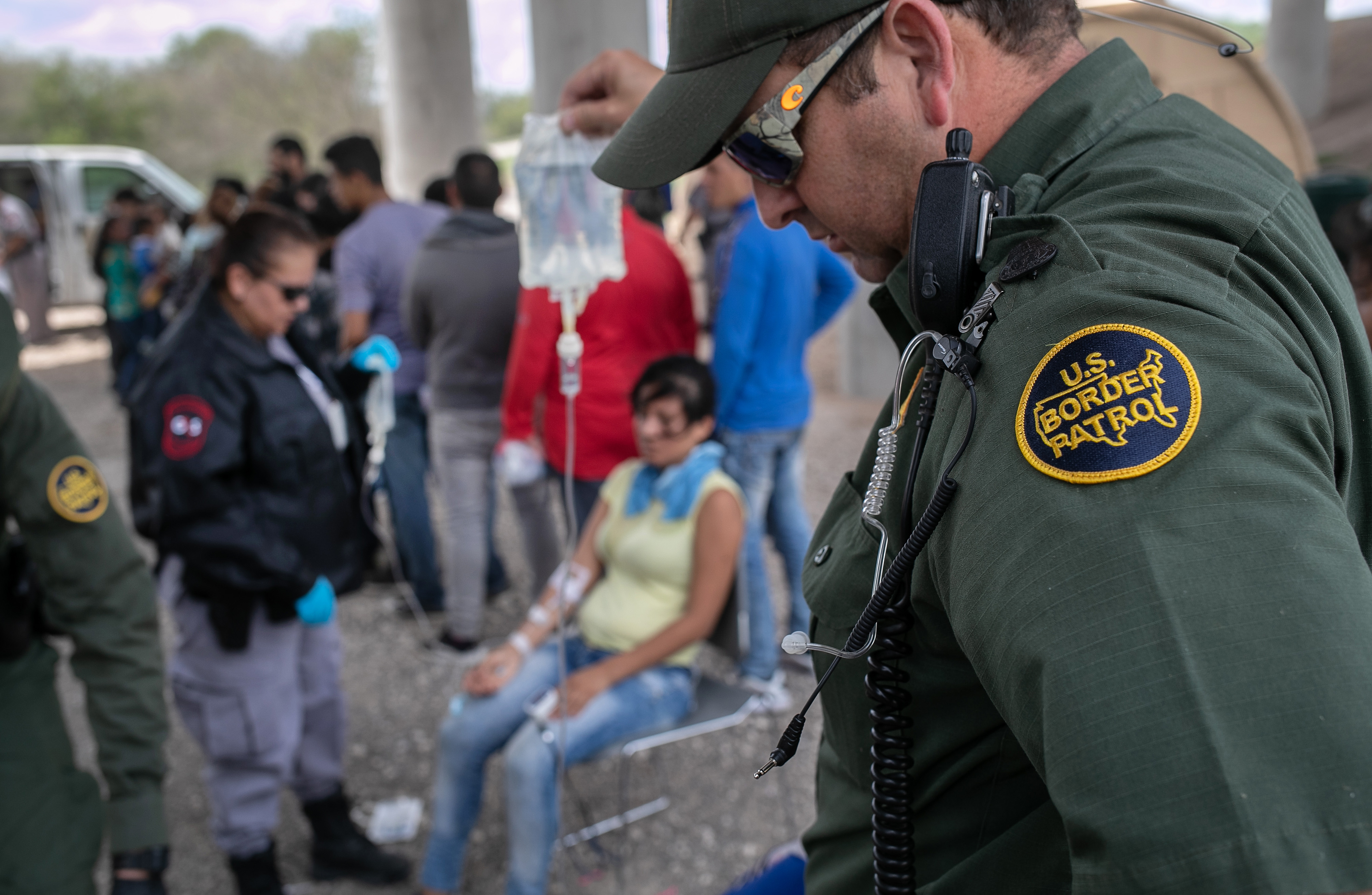 MCALLEN, TEXAS - JULY 02: A U.S. Border Patrol agent holds an IV bag for an immigrant suffering from heat exhaustion after taking her into custody on July 02, 2019 in McAllen, Texas. The immigrants, mostly families from Central America, turned themselves in to border agents after rafting across the Rio Grande from Mexico to seek political asylum in the United States. (Photo by John Moore/Getty Images)