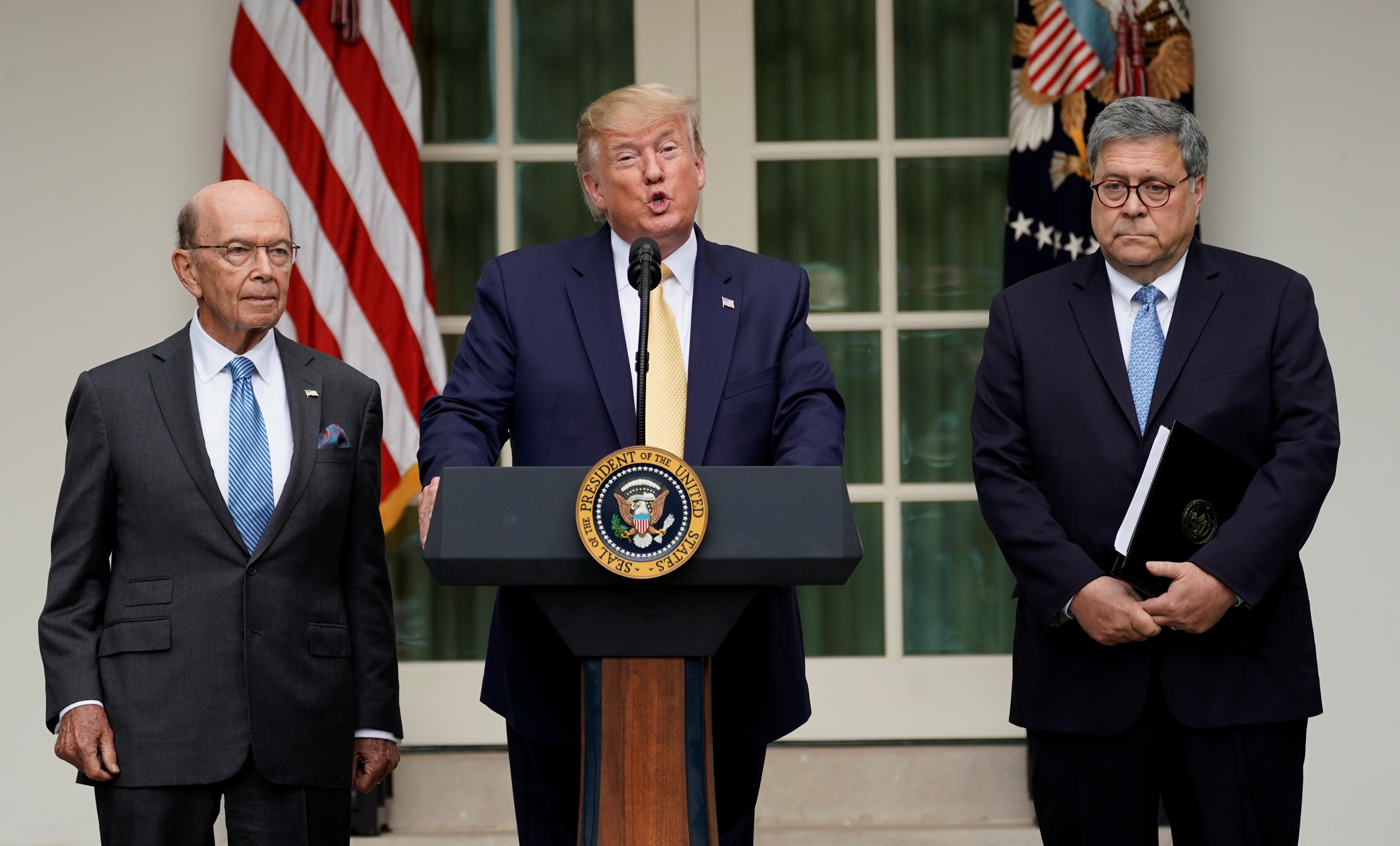 U.S. President Donald Trump stands between Commerce Secretary Wilbur Ross and Attorney General Bill Barr to announce his administration's effort to gain citizenship data during the 2020 census at an event in the Rose Garden of the White House in Washington, U.S., July 11, 2019. REUTERS/Kevin Lamarque