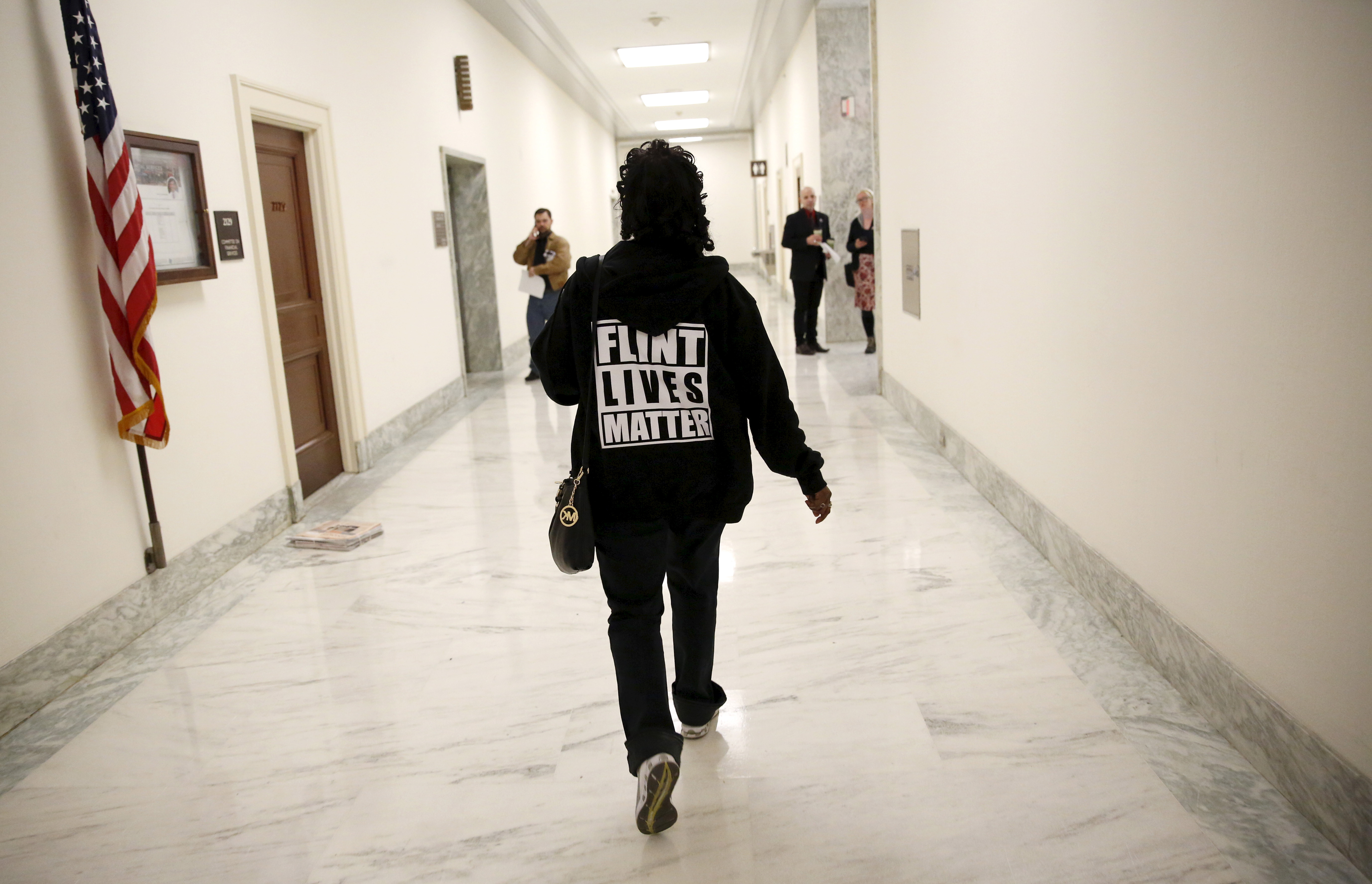 """A woman with a """"Flint Lives Matter"""" shirt walks toward a hearing room where Michigan Governor Rick Snyder and EPA Administrator Gina McCarthy will testify before a House Oversight and government Reform hearing on """"Examining Federal Administration of the Safe Drinking Water Act in Flint, Michigan, Part III"""" on Capitol Hill in Washington March 17, 2016. REUTERS/Kevin Lamarque"""