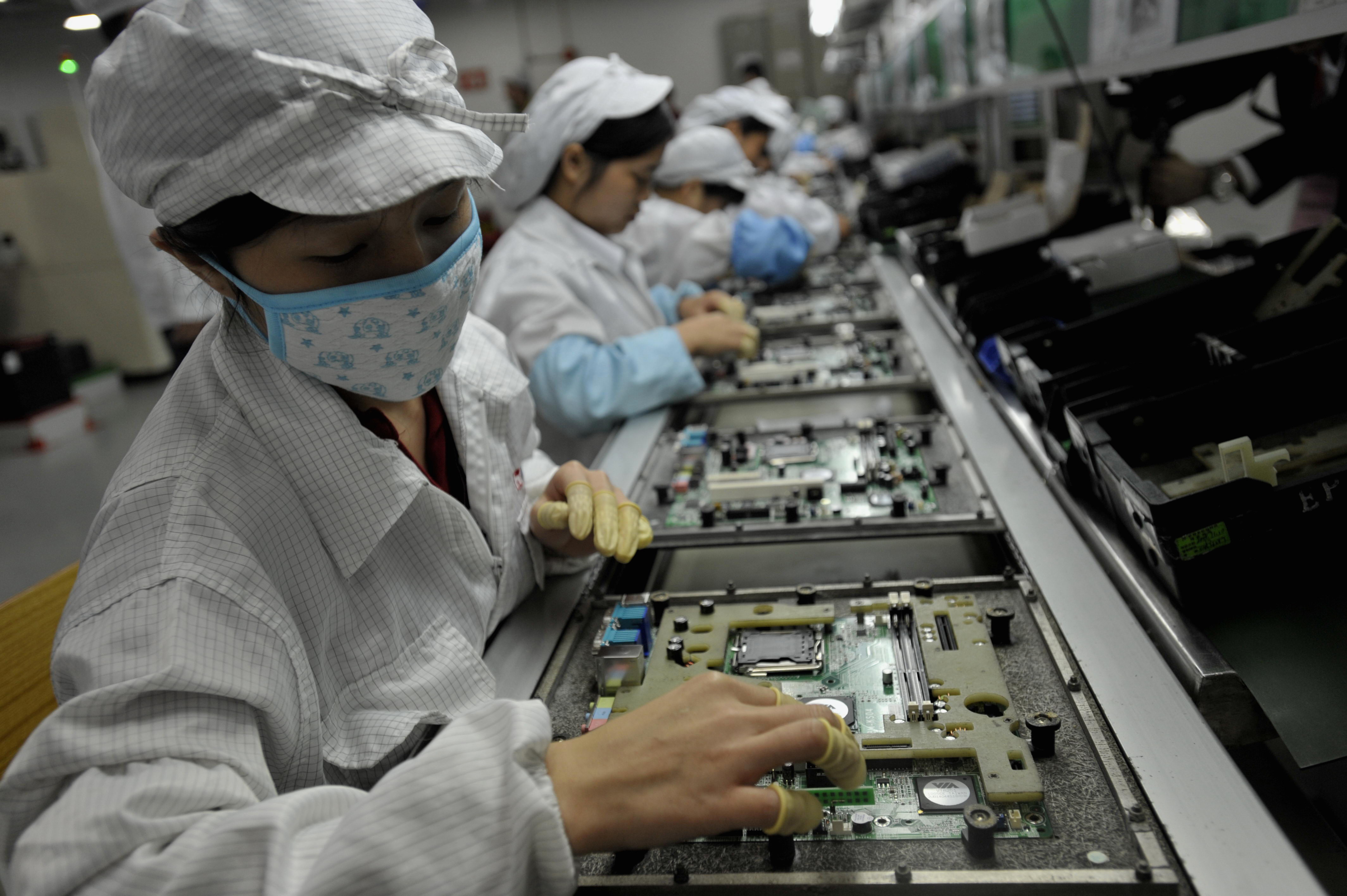 In a picture taken on May 26, 2010 Chinese workers assemble electronic components at the Taiwanese technology giant Foxconn's factory in Shenzhen, in the southern Guangzhou province. Foxconn on June 2 confirmed the death of another employee but denied he died of exhaustion following a spate of suicides at its Chinese plants. (Photo credit should read AFP/AFP/Getty Images)