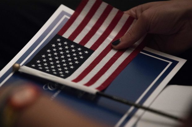 A woman holds the American flag as 31 new citizens from 25 nations are sworn in as new citizens during a naturalization ceremony as part of a celebration of the Constitution and Citizenship Day at the National Archives in Washington, DC on September 17, 2018. (Photo by JIM WATSON/AFP/Getty Images)