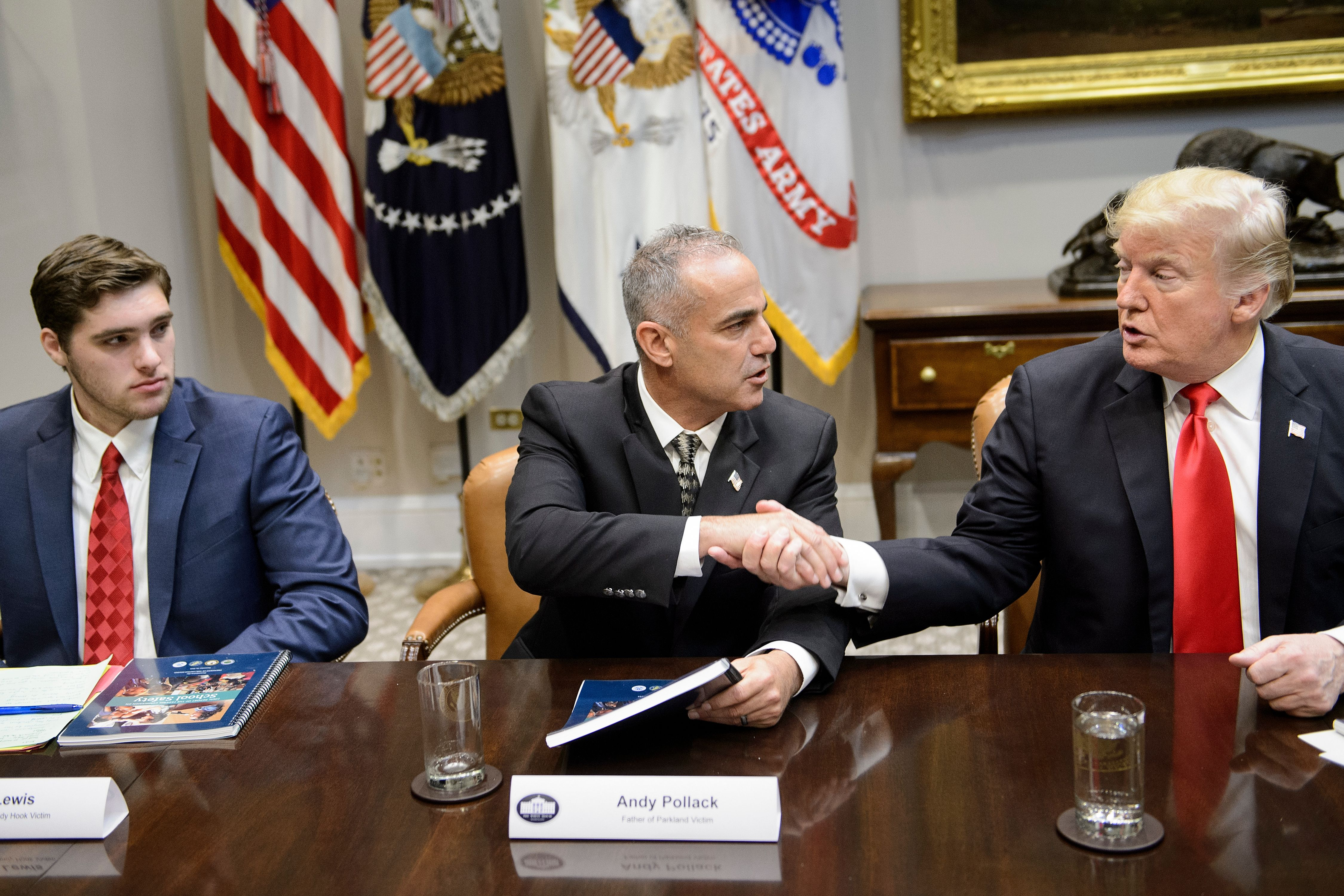 JT Lewis (L), brother of Sandy Hook mass shooting victim Jesse Lewis, watches as Andy Pollack (C), father of Parkland mass shooting victim Meadow Pollack, and US President Donald Trump shake hands during a roundtable discussion about school safety in the Roosevelt Room of the the White House December 18, 2018 in Washington, DC. (Photo by BRENDAN SMIALOWSKI/AFP/Getty Images)