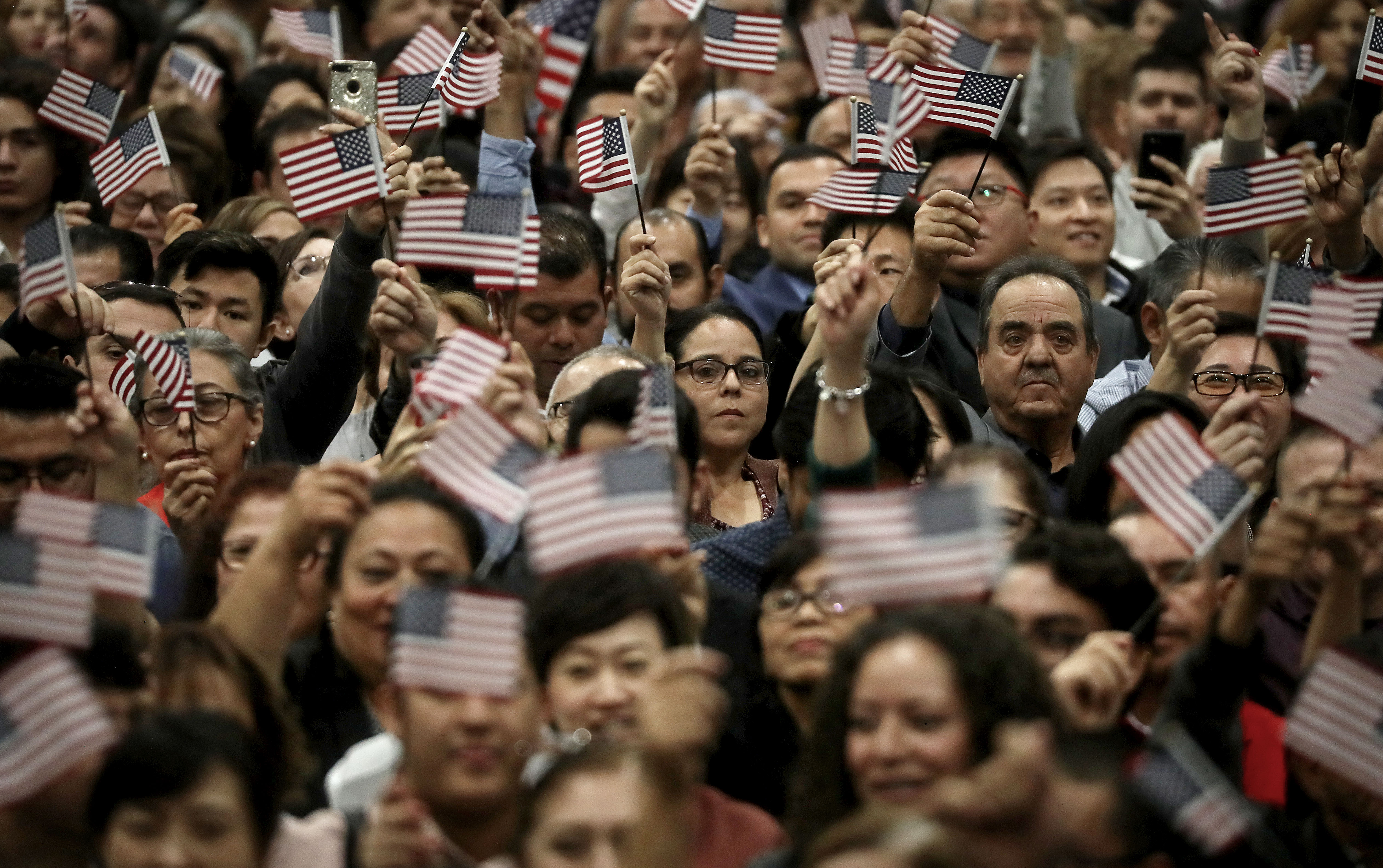 New U.S. citizens wave American flags during a naturalization ceremony on December 19, 2018 in Los Angeles, California. The naturalization ceremony welcomed more than 6,000 immigrants from over 100 countries who took the citizenship oath and pledged allegiance to the American flag. (Mario Tama/Getty Images)