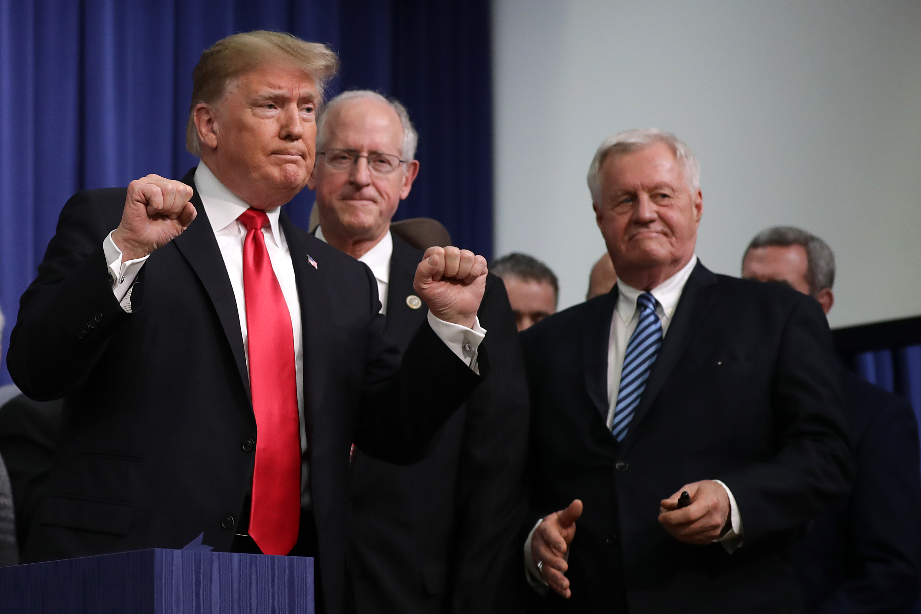 U.S. President Donald Trump (L) pumps his fists after signing the the Agriculture Improvement Act during a ceremony with House Agriculture Committee Chairman Mike Conaway (2nd L) and ranking member Rep. Colin Peterson in the South Court Auditorium of the Eisenhower Executive Office Building December 20, 2018 in Washington, DC. (Photo by Chip Somodevilla/Getty Images)