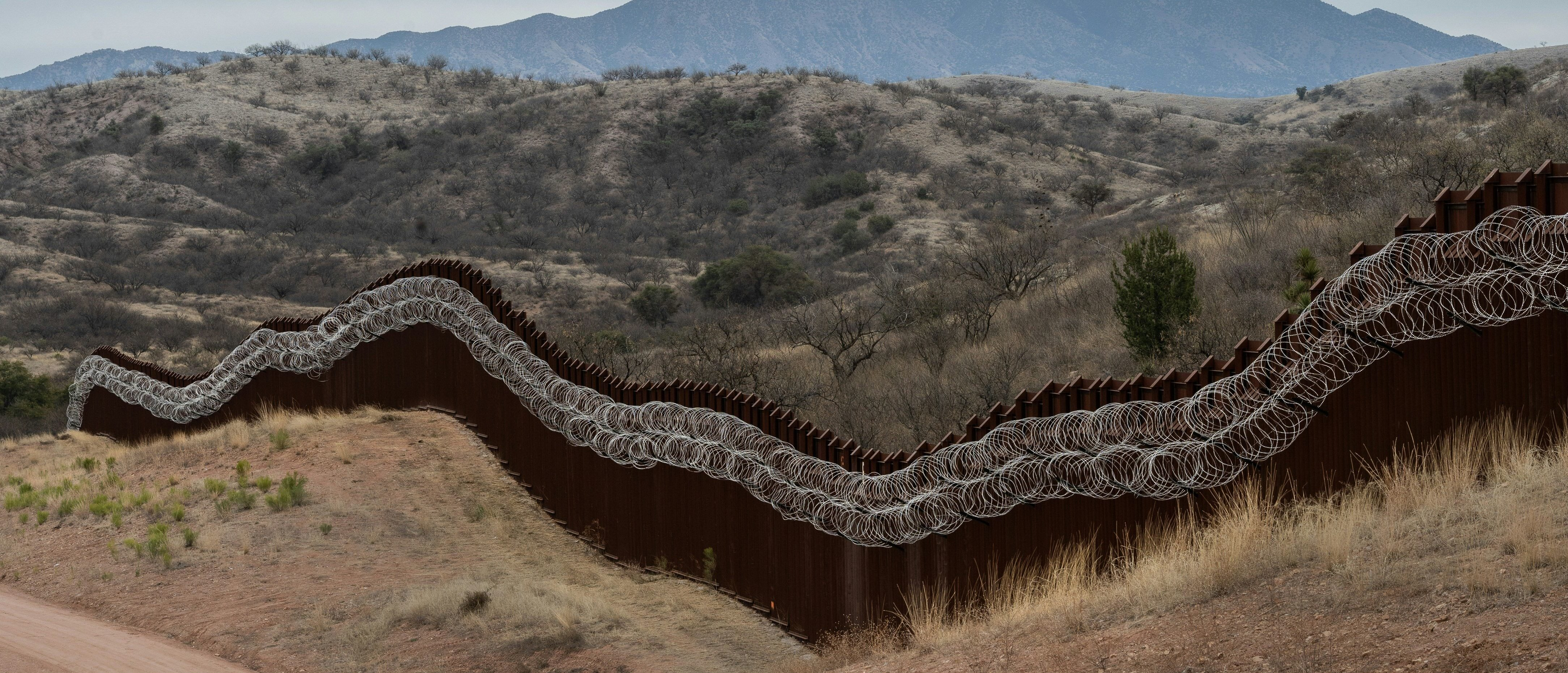 A general view of the US border fence, covered in concertina wire, separating the US and Mexico, at the outskirts of Nogales, Arizona, on February 9, 2019. (ARIANA DREHSLER/AFP/Getty Images)