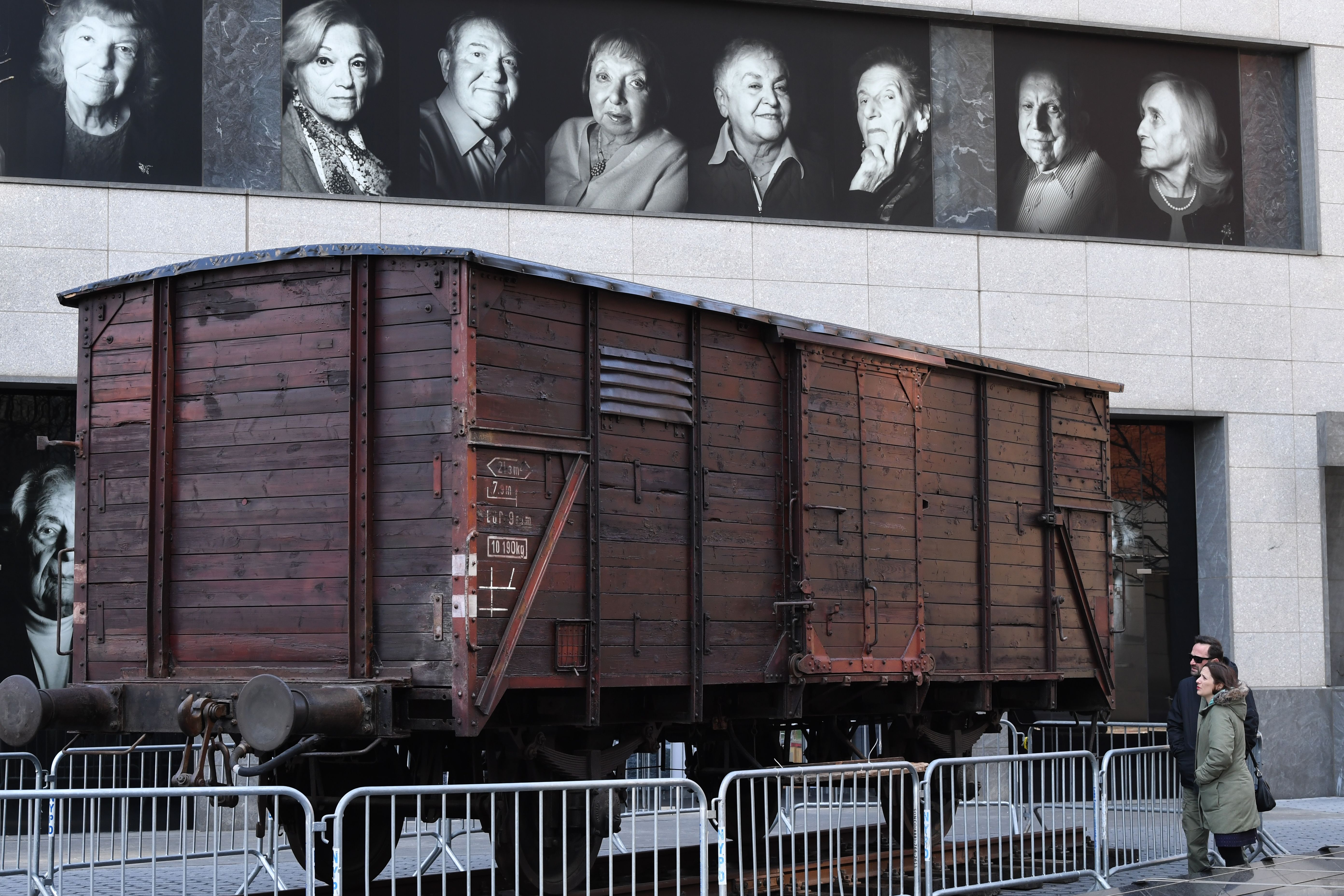 Portraits of Holocaust survivors are displayed on April 2, 2019 at the Museum of Jewish Heritage, as a vintage German train car, like those used to transport people to Auschwitz and other Nazi death camps, is seen in front of the building in New York. (TIMOTHY A. CLARY/AFP/Getty Images)