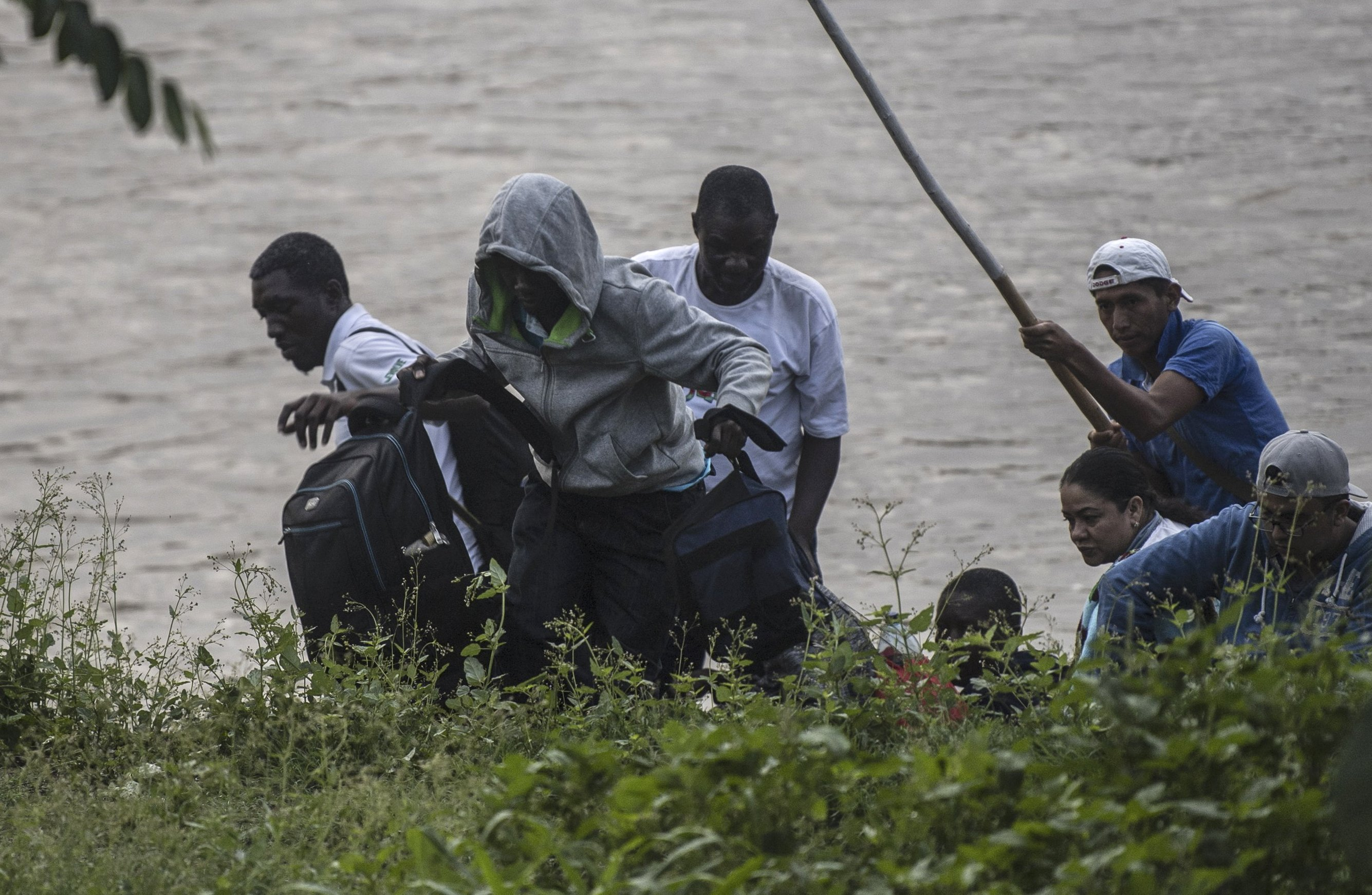 "African migrants and locals arrive in Ciudad Hidalgo in Chiapas State, Mexico, after illegally crossing the Suchiate river from Tecun Uman in Guatemala on a makeshift raft, on June 10, 2019. - In the framework of Mexico's deal to curb migration in order to avert US President Donald Trump's threat of tariffs, Mexico's Foreign Minister Marcelo Ebrard said Mexico will discuss a ""safe third country"" agreement with the US -- in which migrants entering Mexican territory must apply for asylum there rather than in the US -- if the flow of undocumented immigrants continues. (Photo by Pedro PARDO / AFP) (Photo credit should read PEDRO PARDO/AFP/Getty Images)"