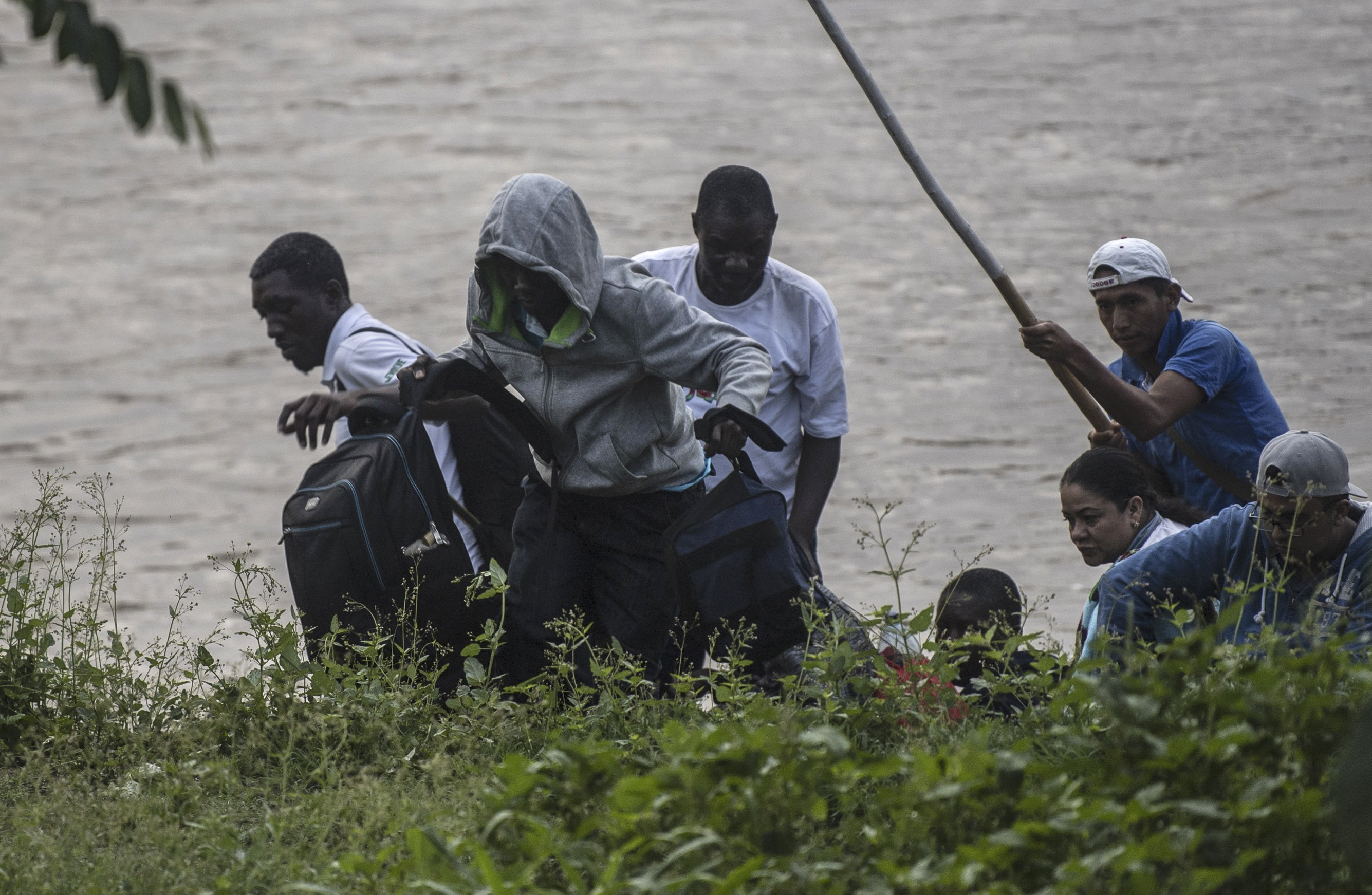 African migrants and locals arrive in Ciudad Hidalgo in Chiapas State, Mexico, after illegally crossing the Suchiate river from Tecun Uman in Guatemala on a makeshift raft, on June 10, 2019. - In the framework of Mexico's deal to curb migration in order to avert US President Donald Trump's threat of tariffs, Mexico's Foreign Minister Marcelo Ebrard said Mexico will discuss a