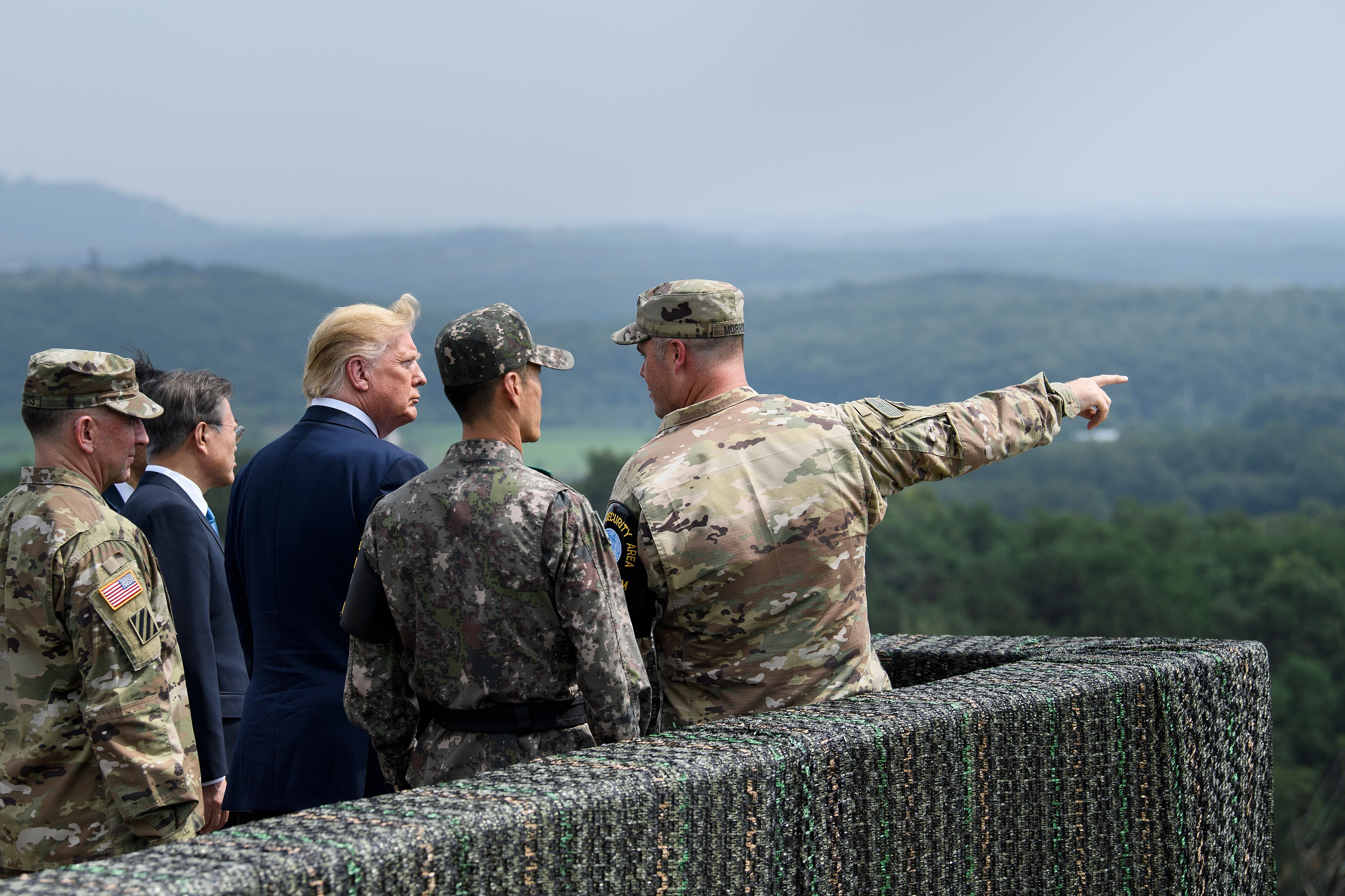 US President Donald Trump (C) and South Korean President Moon Jae-in (2nd L, obscured) visit an observation post in the Joint Security Area (JSA) at Panmunjom in the Demilitarized Zone (DMZ) separating North and South Korea on June 30, 2019. (Photo by BRENDAN SMIALOWSKI/AFP/Getty Images)