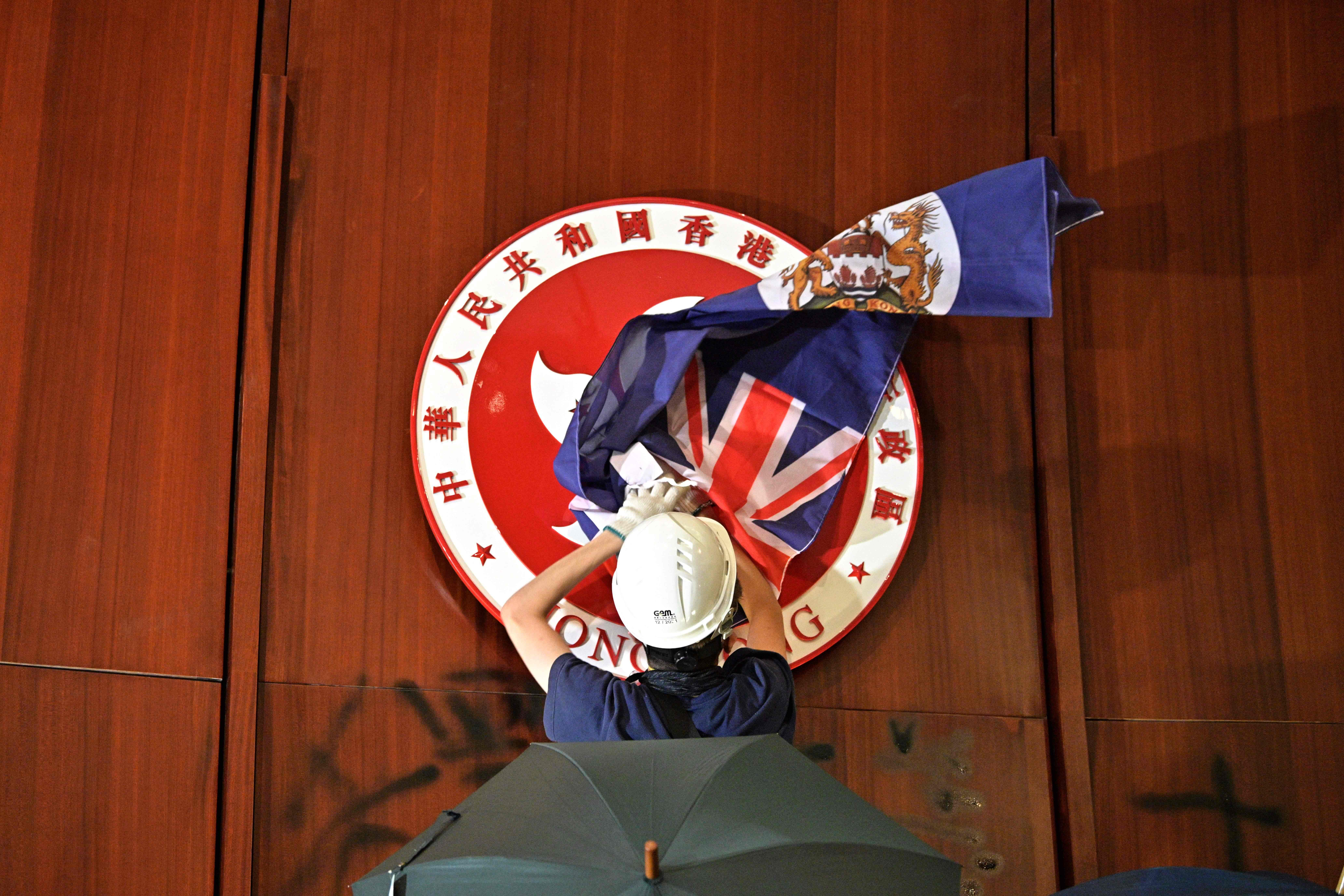 TOPSHOT - A protester attempts to cover the Hong Kong emblem with a British colonial flag after they broke into the government headquarters in Hong Kong on July 1, 2019, on the 22nd anniversary of the city's handover from Britain to China. - Anti-government protesters stormed Hong Kong's parliament building late on July 1 after successfully smashing their way through reinforced glass windows and prizing open metal shutters that were blocking their way. (Photo by Anthony WALLACE / AFP/ Getty Images)