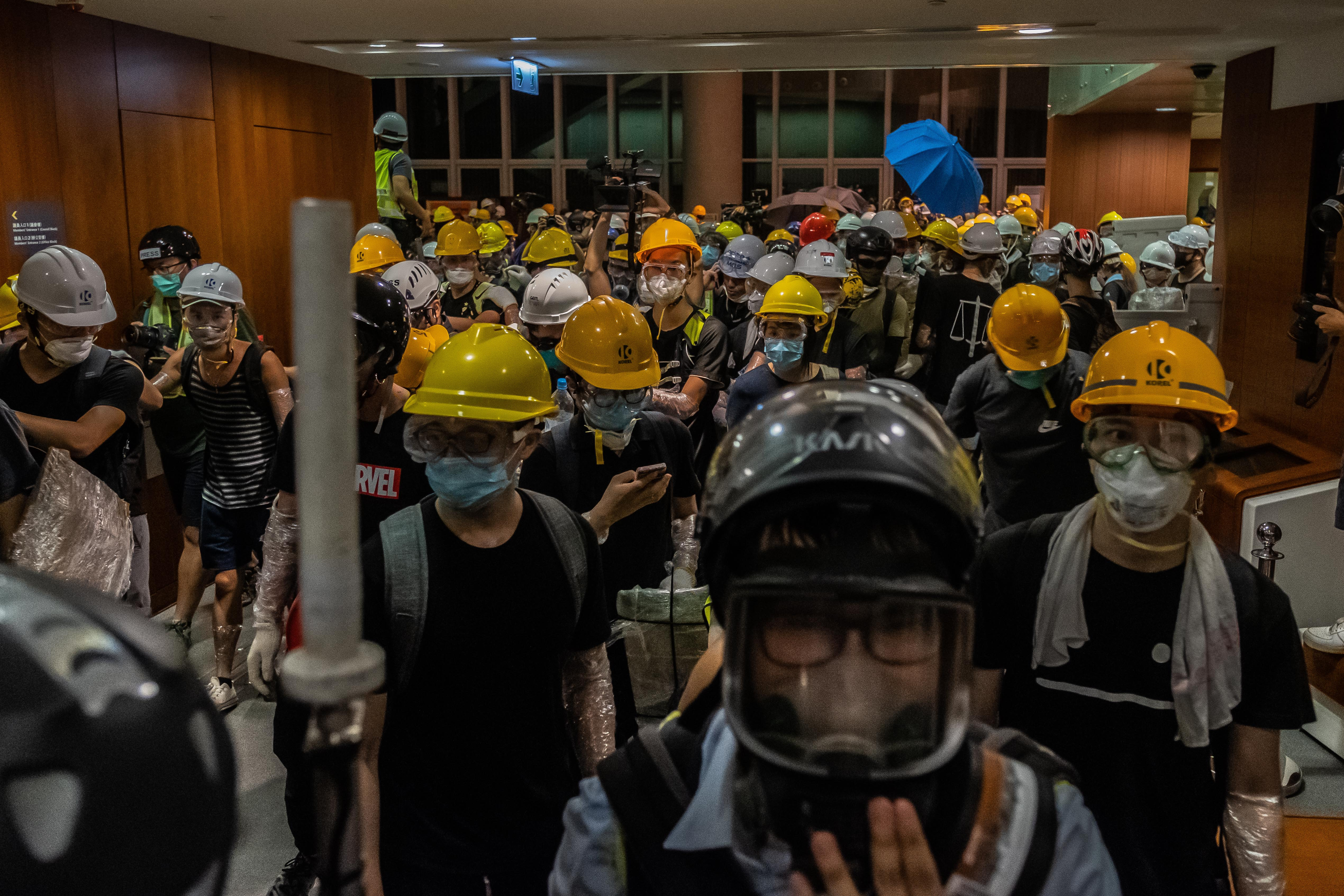 Protesters break into the Legislative Council Complex protest against the extradition bill on July 1, 2019 in Hong Kong, China. Hundreds of pro-democracy protesters broke into Hong Kong's legislature on Monday during the 22nd anniversary of the territory's return to China from Britain after riot police officers used batons and pepper spray to push back demonstrators. The city's embattled leader Carrie Lam watched a flag-raising ceremony on a video display from inside a convention center, citing bad weather, as tens of thousands protesters marched separately after the ceremony that morning. (Photo by Billy H.C. Kwok/Getty Images)