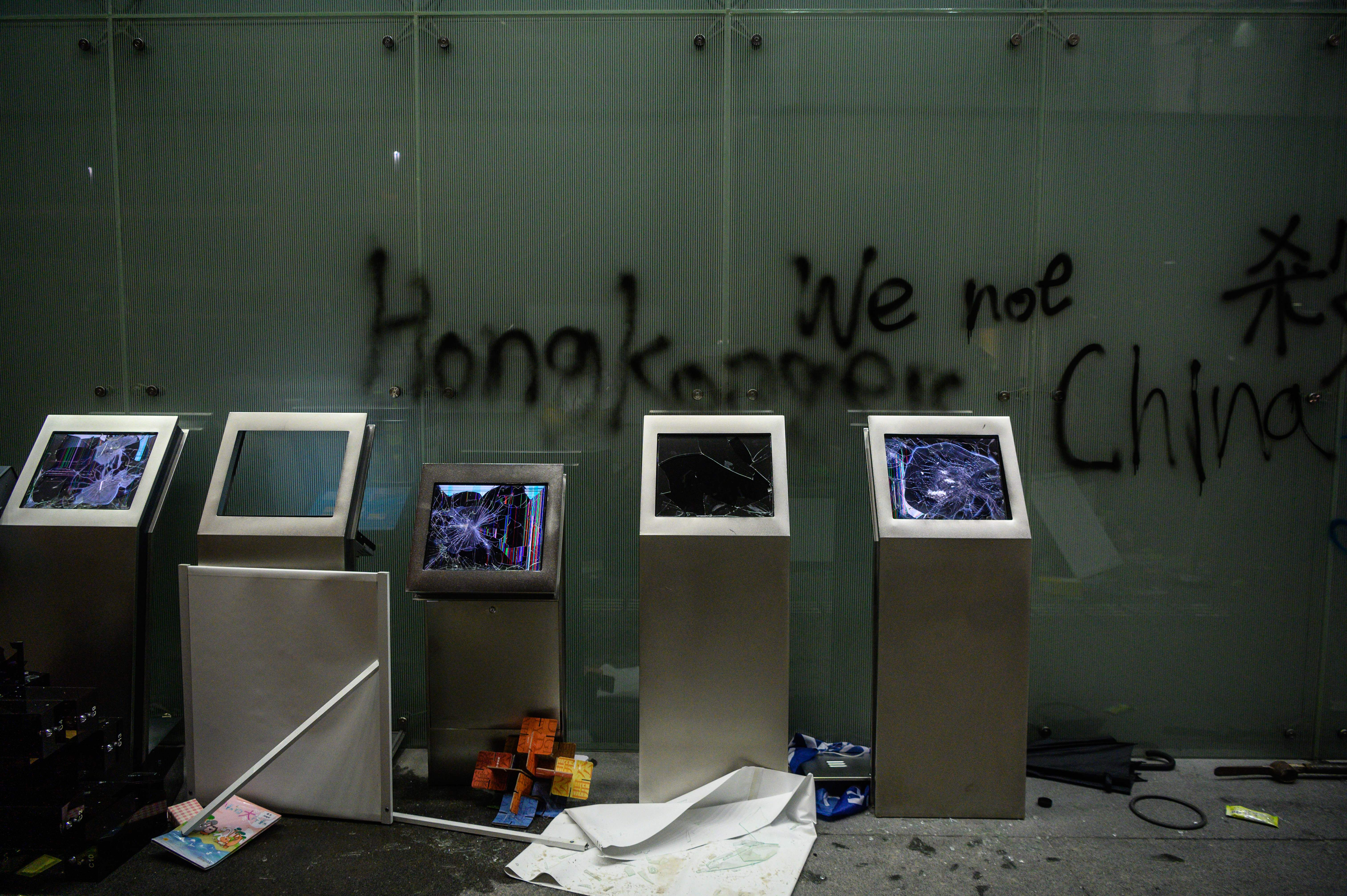 Smashed monitors and graffiti are seen after protesters stormed the government headquarters hours before in Hong Kong early on July 2, 2019. - Hong Kong police fired tear gas early on July 2 to regain control of the city's parliament after thousands of protesters occupied and ransacked the assembly in an unprecedented display of defiance on the anniversary of the territory's handover to China. (ANTHONY WALLACE/AFP/Getty Images)