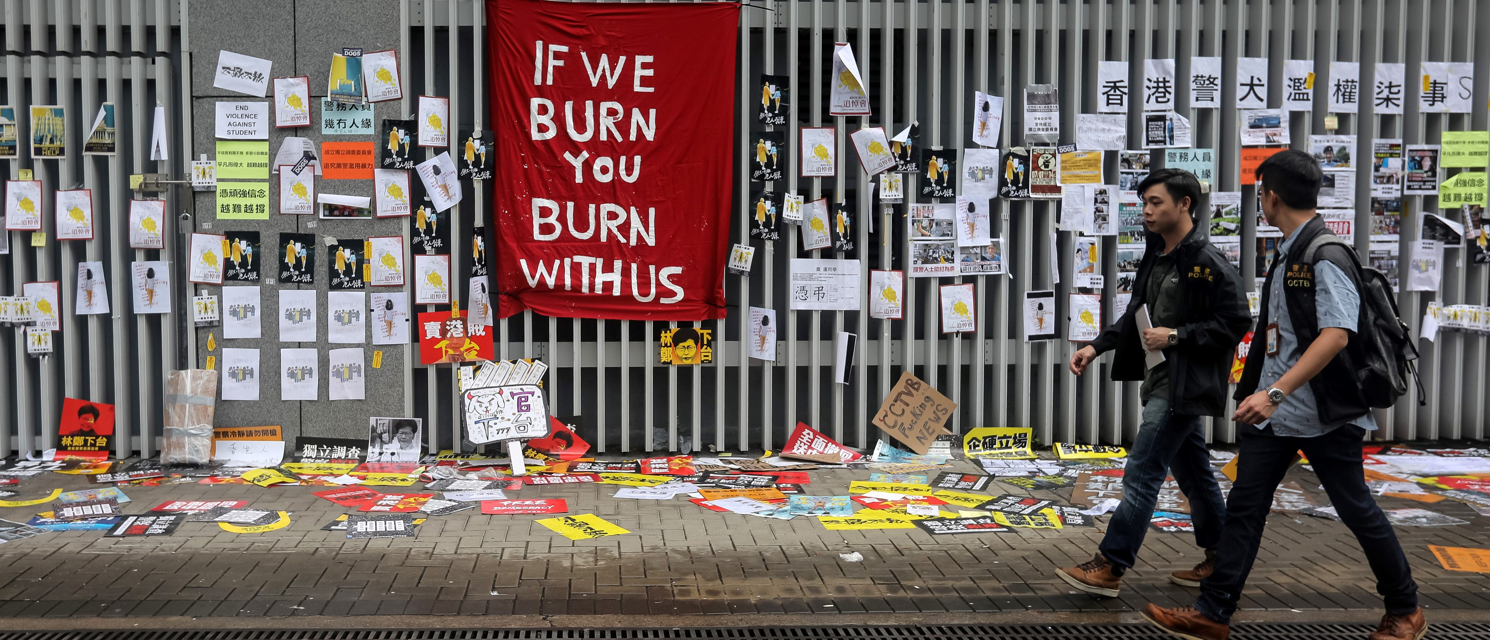 """Police walk past signs and posters outside the government headquarters in Hong Kong on July 2, 2019, a day after protesters broke into the building. - Hong Kong's leader on July 2 condemned """"the extreme use of violence"""" by masked protesters who stormed and ransacked the city's legislature in an unprecedented challenge to Beijing's authority. (VIVEK PRAKASH/AFP/Getty Images)"""