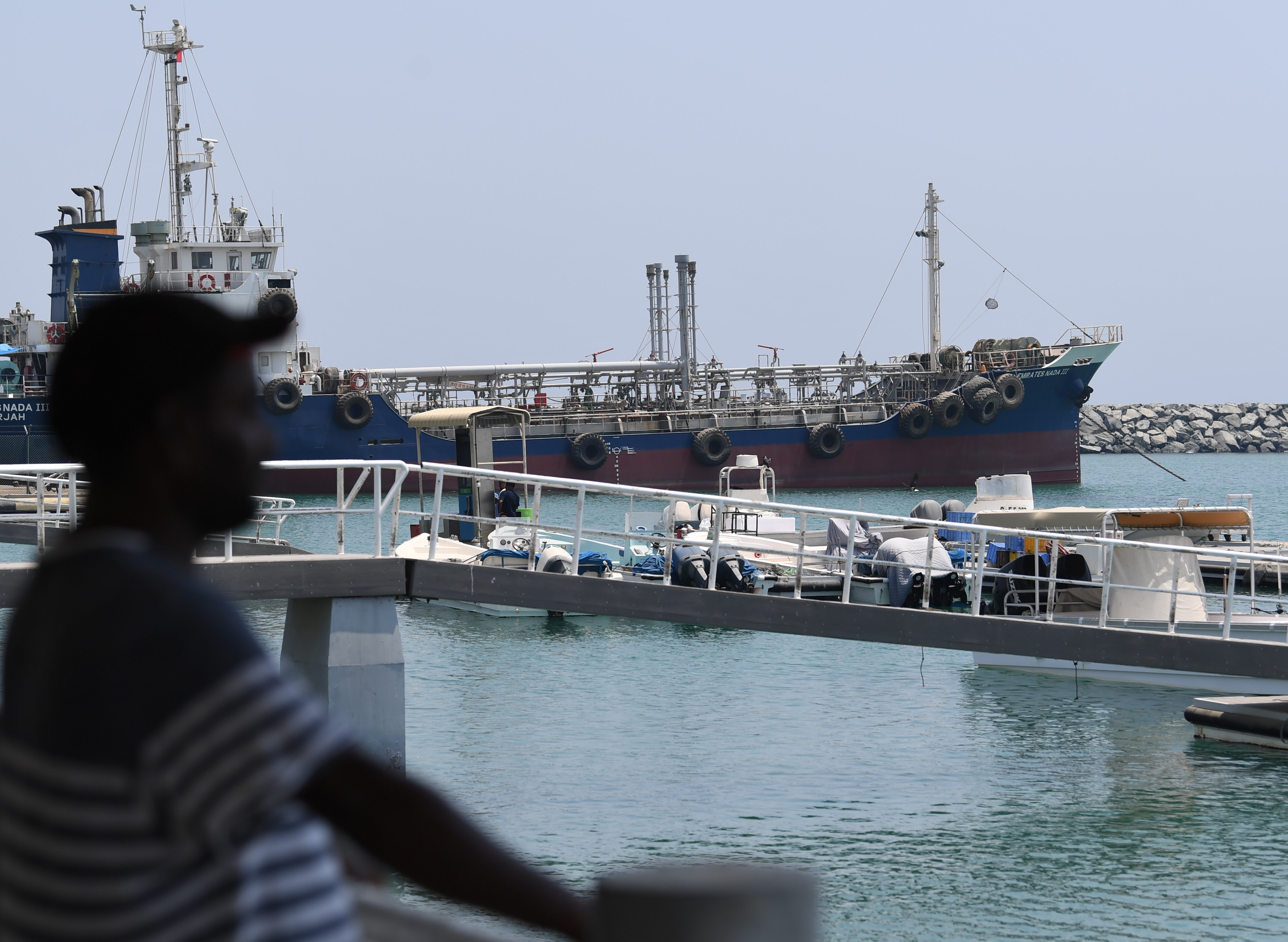 A man watches on July 2, 2019 the ships movement in the port of Fujairah in the east of the United Arab Emirates (UAE), where recent tensions spiraling between Iran and the United States have affected movement in the Gulf of Oman, near the strategic Strait of Hormuz. (Photo by KARIM SAHIB / AFP) (Photo credit should read KARIM SAHIB/AFP/Getty Images)