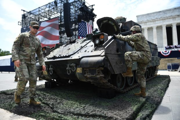 "Members of the US military are seen next to a Bradley Fighting Vehicle as preparations are made for the ""Salute to America"" Fourth of July event with US President Donald Trump at the Lincoln Memorial on the National Mall in Washington, DC, July 3, 2019, which will feature flyovers by the Blue Angels, an airplane used as Air Force One, as well as military demonstrations and a speech by Trump. (Photo by BRENDAN SMIALOWSKI/AFP/Getty Images)"