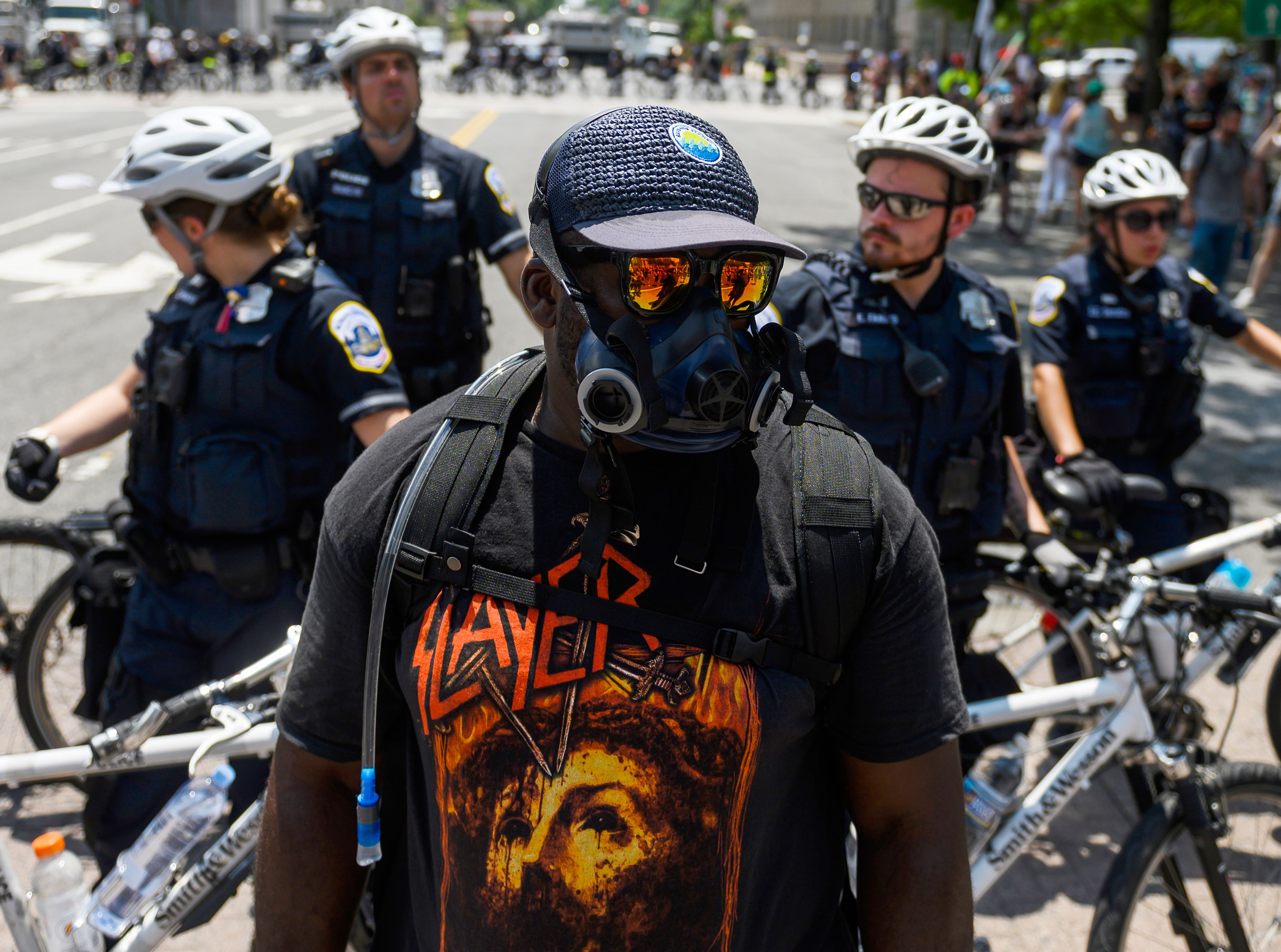 "A member of an anti-fascist or Antifa group stands in front of police as the Alt-Right movement gathers for a ""Demand Free Speech"" rally in Washington, DC, on July 6, 2019. (Photo by ANDREW CABALLERO-REYNOLDS / AFP) (Photo credit should read ANDREW CABALLERO-REYNOLDS/AFP/Getty Images)"