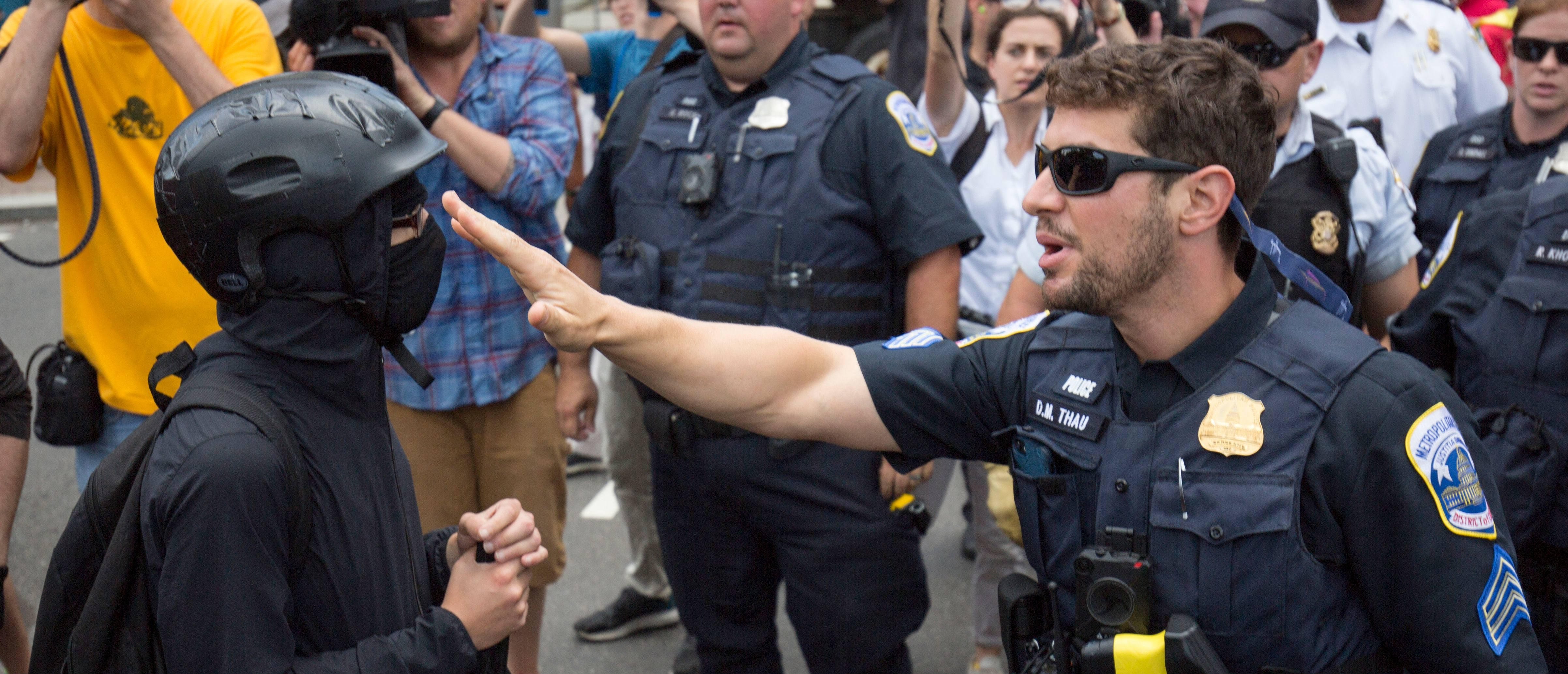 """A member of an anti-fascist or Antifa group (L) argues with police as they try to reach the Alt-Right """"Demand Free Speech"""" rally in Washington, DC, July 6, 2019. (Photo by Alastair Pike / AFP) (Photo credit should read ALASTAIR PIKE/AFP/Getty Images)"""