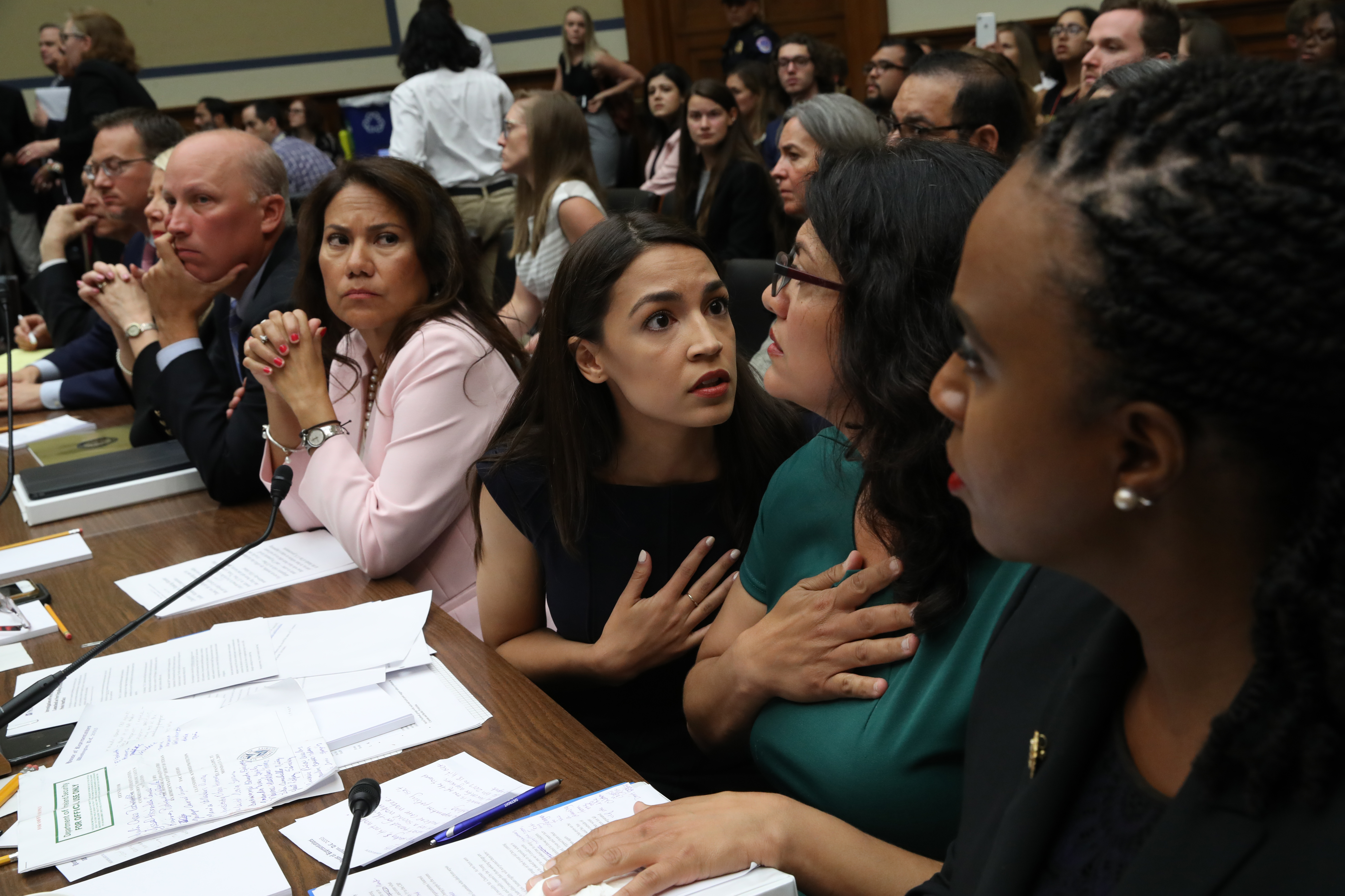 "U.S. Rep. Alexandria Ocasio-Cortez (D-NY) (3R) speaks with Rep. Rashida Tlaib (D-MI) (2R) as U.S. Rep. Veronica Escobar (D-TX) (4R) and Rep. Ayanna S. Pressley (D-MA) (R) look on during a House Oversight and Reform Committee holds a hearing on ""The Trump Administration's Child Separation Policy: Substantiated Allegations of Mistreatment."" July 12, 2019 in Washington, DC. (Photo by Win McNamee/Getty Images)"