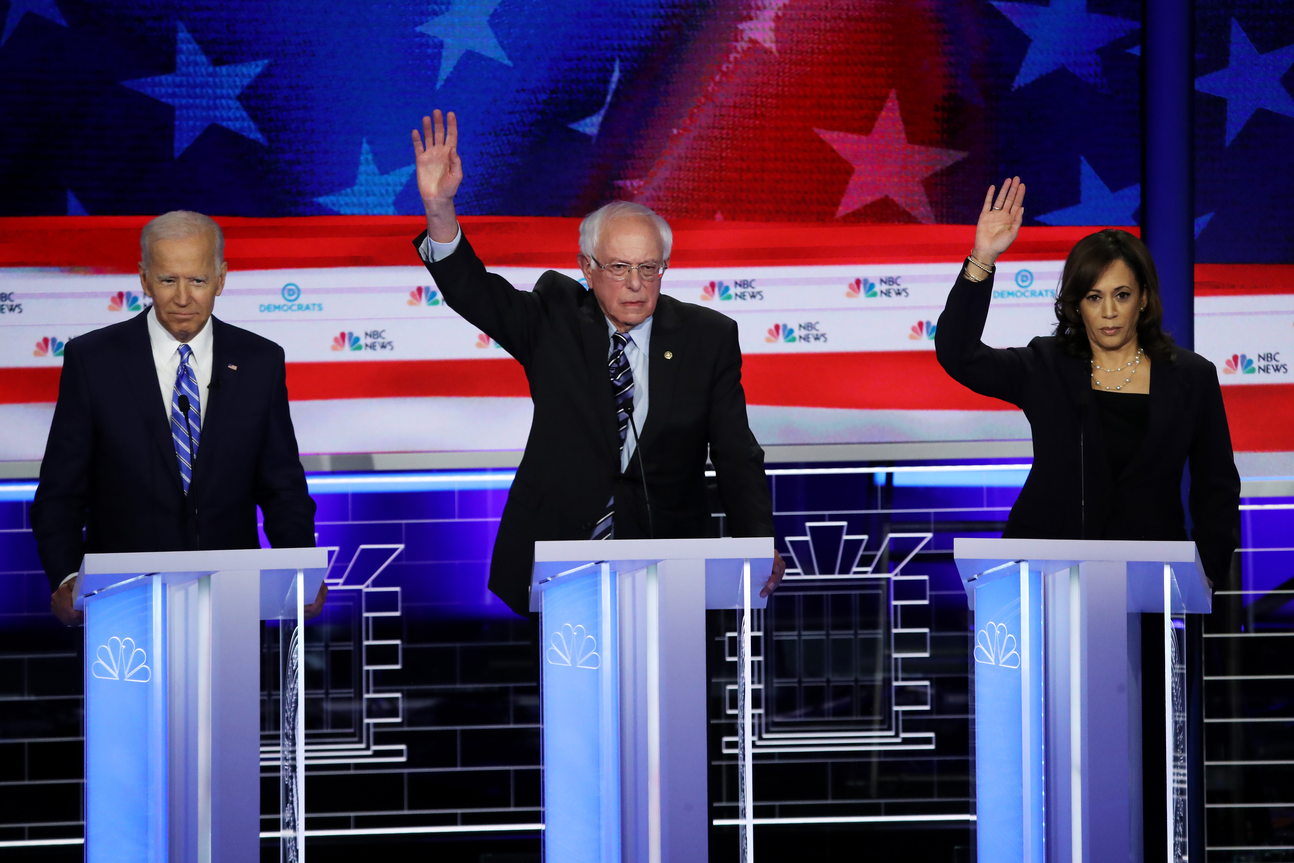 Former Vice President Joe Biden looks on as Sen. Bernie Sanders and Sen. Kamala Harris raise their hands during the second night of the first Democratic presidential debate on June 27, 2019 in Miami, Florida. (Photo by Drew Angerer/Getty Images)