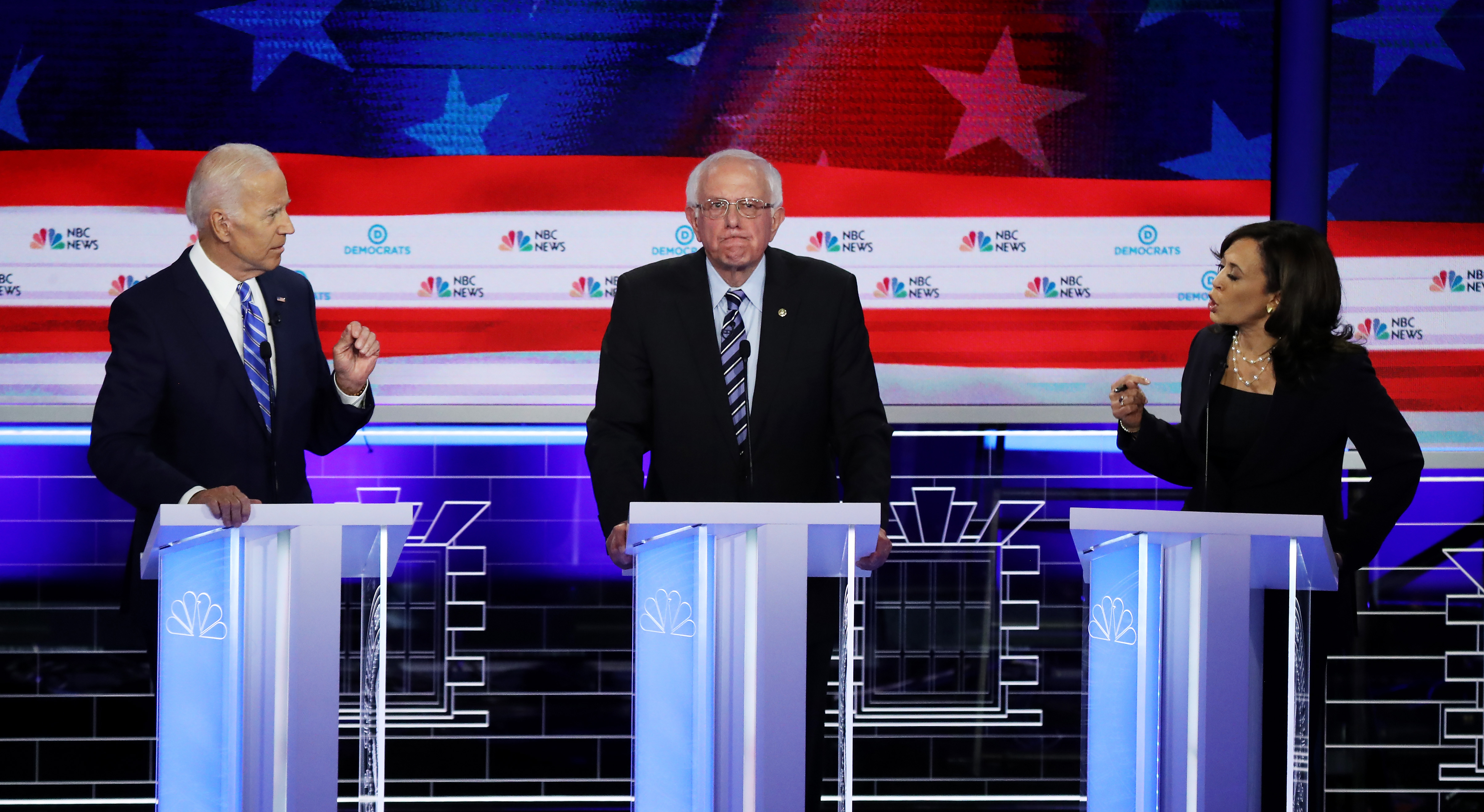 Sen. Kamala Harris (R) (D-CA) and former Vice President Joe Biden (L) speak as Sen. Bernie Sanders (I-VT) looks on during the second night of the first Democratic presidential debate on June 27, 2019 in Miami, Florida. A field of 20 Democratic presidential candidates was split into two groups of 10 for the first debate of the 2020 election, taking place over two nights at Knight Concert Hall of the Adrienne Arsht Center for the Performing Arts of Miami-Dade County, hosted by NBC News, MSNBC, and Telemundo. (Photo by Drew Angerer/Getty Images)