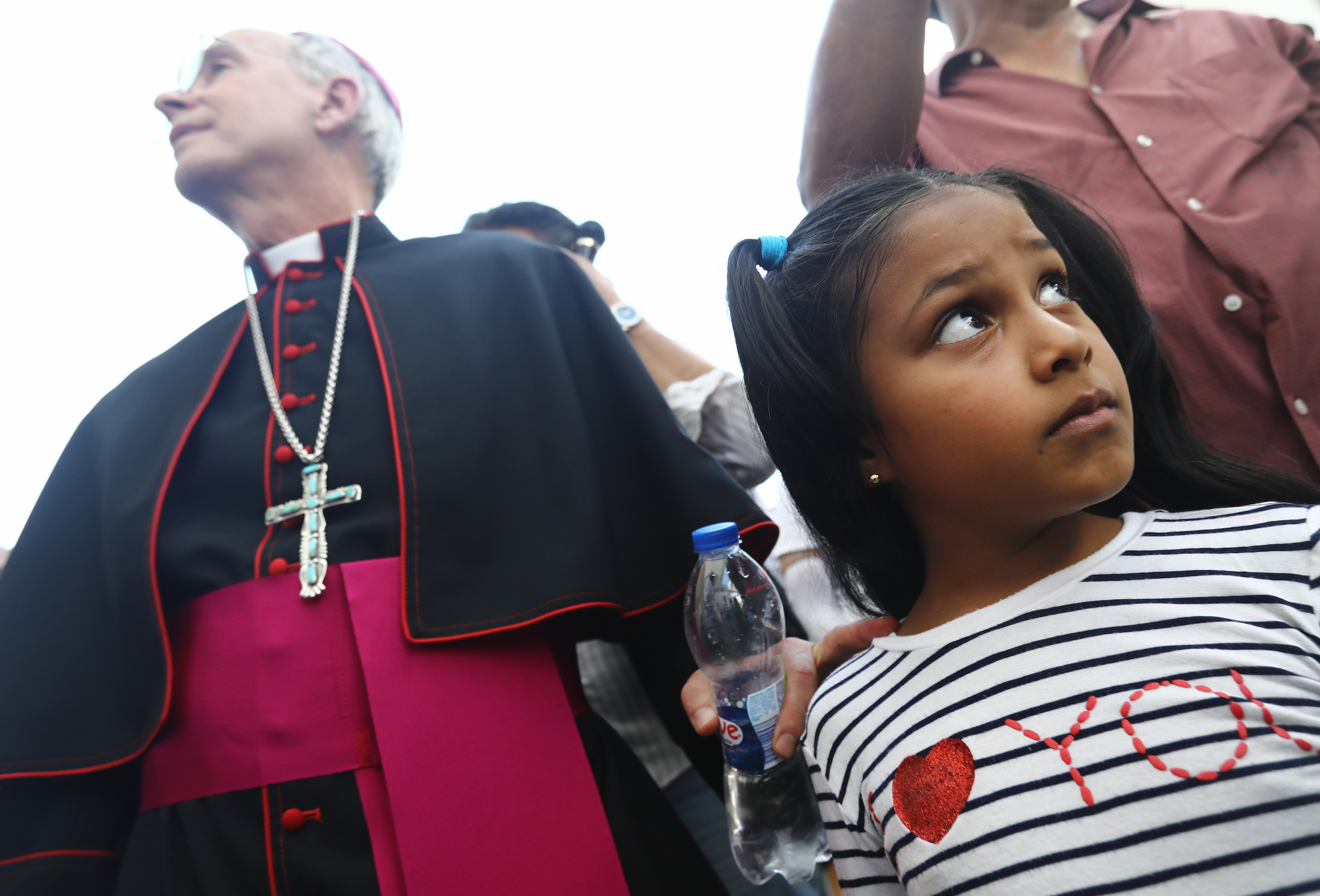 CIUDAD JUAREZ, MEXICO - JUNE 27: El Paso Bishop Mark Seitz (L) prepares to escort Celsia Palma, 9, from Honduras, before they cross the Paso Del Norte Port of Entry bridge towards the U.S. on June 27, 2019, in Ciudad Juarez, Mexico. Seitz escorted Celsia and other family members across the port of entry to be processed by U.S. immigration authorities. Earlier, Seitz and clergy from the Diocese of Ciudad Juarez held a prayer with migrants who were recently returned to Ciudad Juarez from El Paso because of the controversial 'Remain in Mexico' policy. (Photo by Mario Tama/Getty Images)