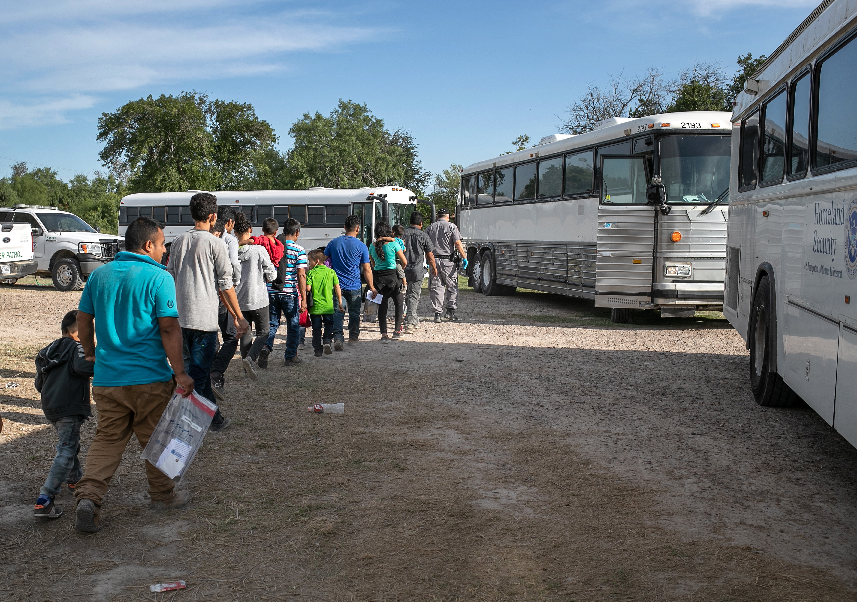 LOS EBANOS, TEXAS - JULY 02: Immigrants walk to U.S. Homeland Security busses to be transferred to a U.S. Border Patrol facility in McAllen after crossing from Mexico on July 02, 2019 in Los Ebanos, Texas. A group of hundreds of immigrants, most from Central America, turned themselves in to Border Patrol agents after rafting across the Rio Grande from Mexico to seek political asylum in the United States. (Photo by John Moore/Getty Images)