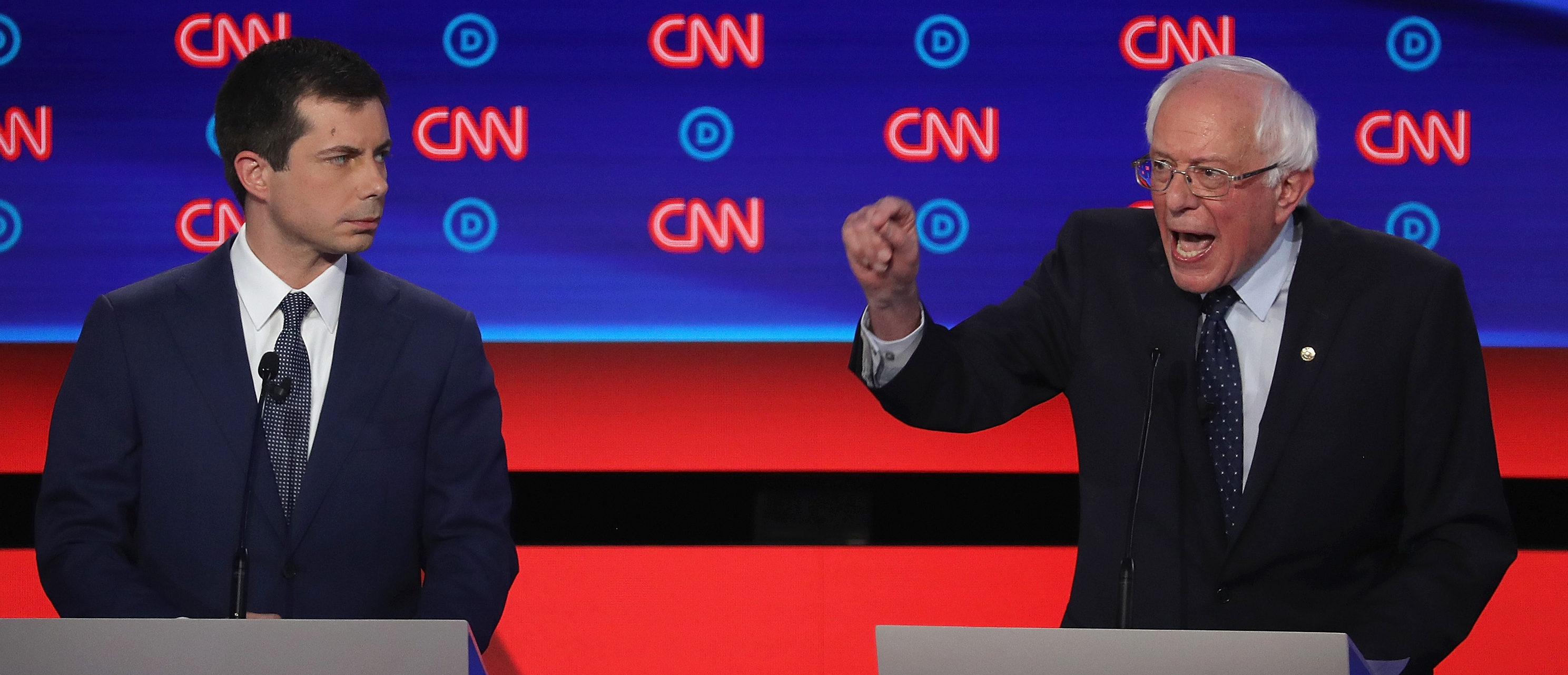 Democratic presidential candidate Sen. Bernie Sanders (I-VT) (R) speaks while South Bend, Indiana Mayor Pete Buttigieg listens during the Democratic Presidential Debate at the Fox Theatre July 30, 2019 in Detroit, Michigan. (Justin Sullivan/Getty Images)