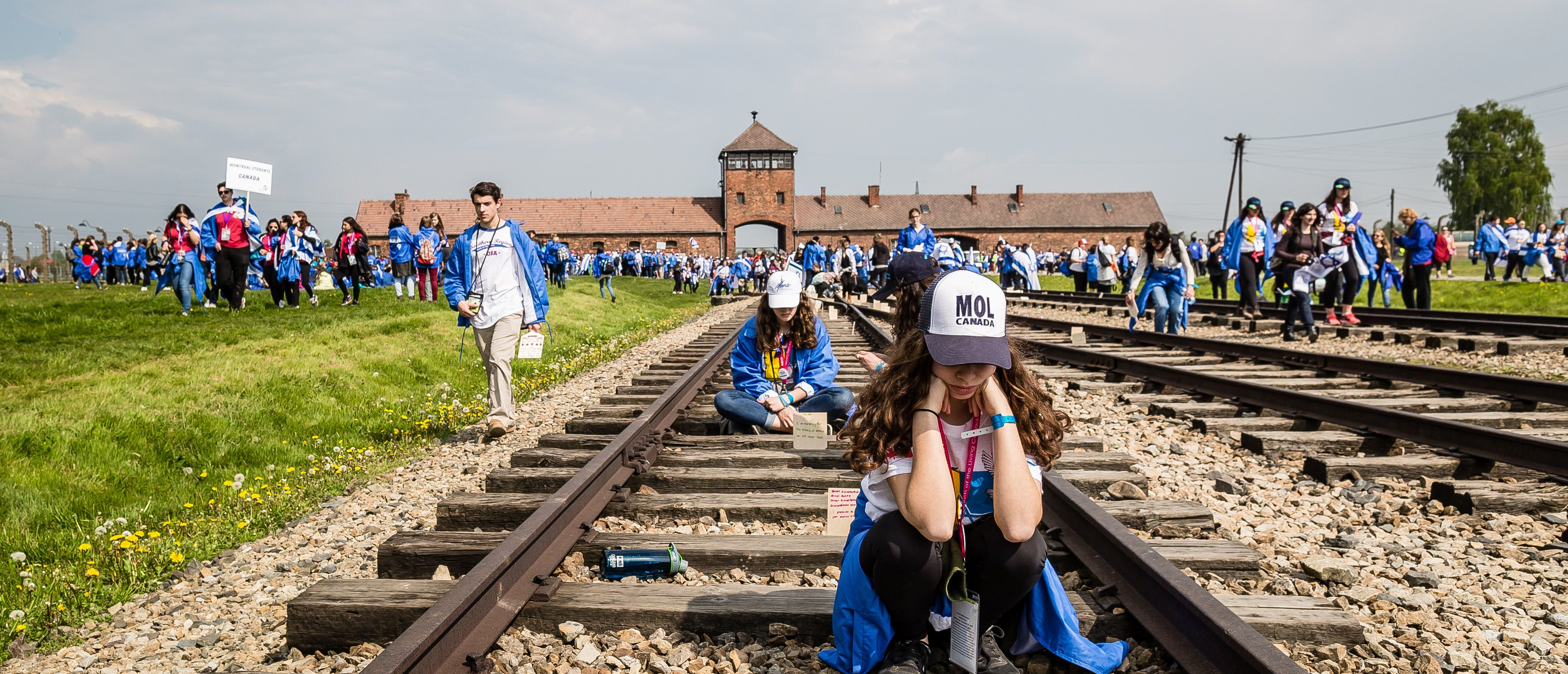 "Participants of the annual ""March of the Living"" are seen on railtracks leading to the former Auschwitz-Birkenau Nazi death camp in Brzezinka (Birkenau) near Oswiecim (Auschwitz), Poland, on May 5, 2016. Thousands of young Jews from 40 nations marched alongside a handful of Holocaust survivors and Polish teenagers in homage to the victims of the former Auschwitz-Birkenau WWII death camp in southern Poland. (Photo: WOJTEK RADWANSKI/AFP/Getty Images)"