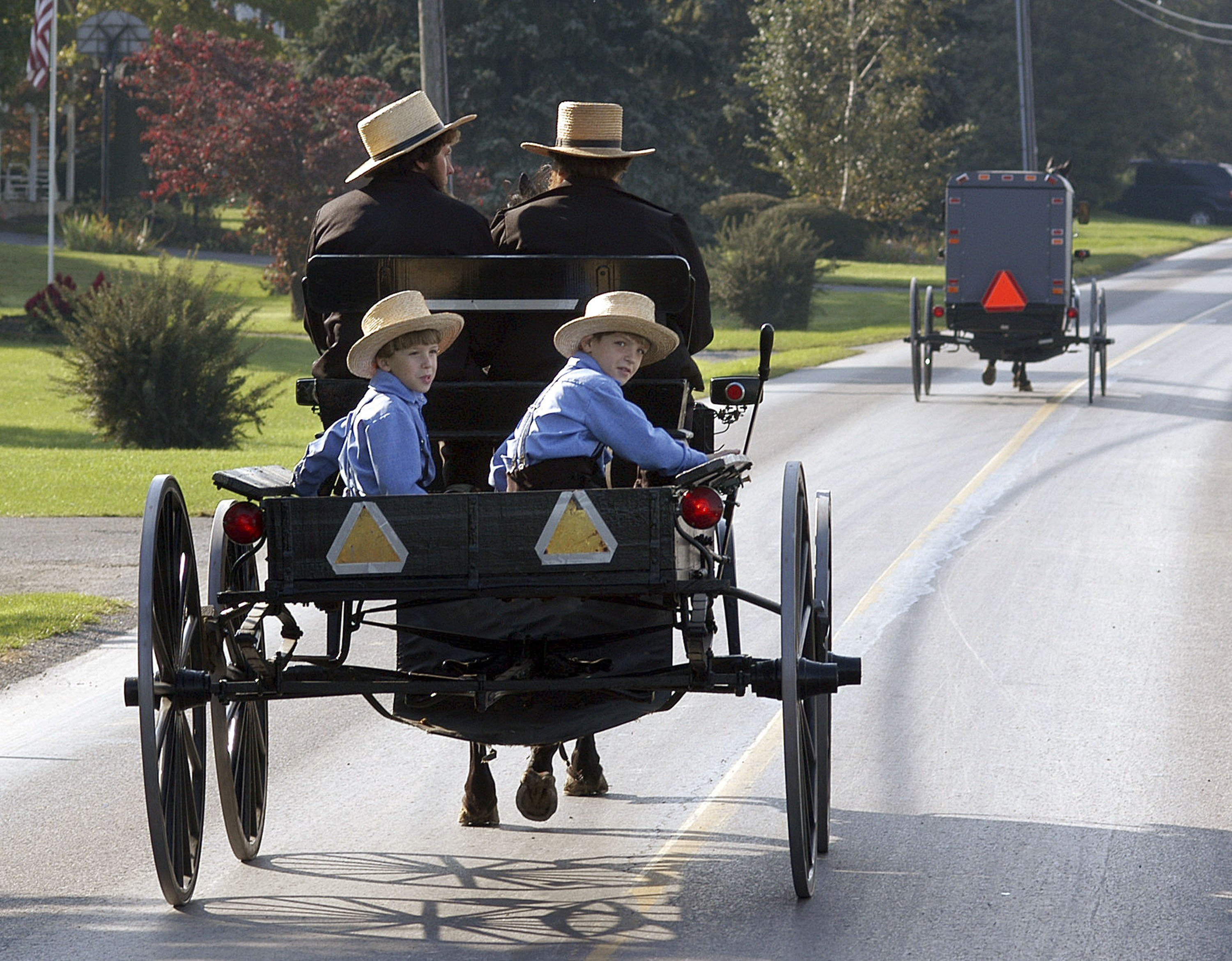 A group of Amish children ride in a buggy near a one room Amish school house. (Photo by William Thomas Cain/Getty Images)