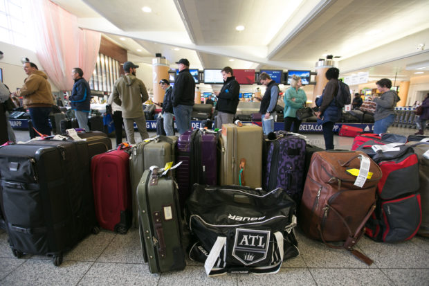 ATLANTA, GA - DECEMBER 18: Passengers search for their luggage near rows of unclaimed baggage at Hartsfield-Jackson Atlanta International Airport on December 18, 2017 in Atlanta, Georgia. Hundreds of flights were cancelled after a power outage at the airport. (Photo by Jessica McGowan/Getty Images)