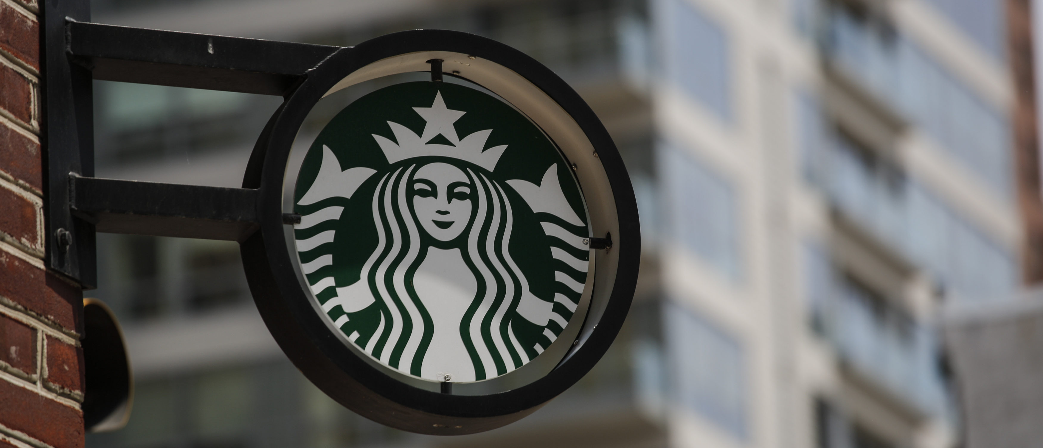 The Starbucks logo it's seen outside a store on May 29, 2018 in Philadelphia. - Starbucks is closing more than 8,000 stores across the United States Tuesday to conduct employee training on racial bias, a closely watched exercise that spotlights lingering problems of discrimination nationwide. (Photo by KENA BETANCUR / AFP) (Photo credit should read KENA BETANCUR/AFP/Getty Images)