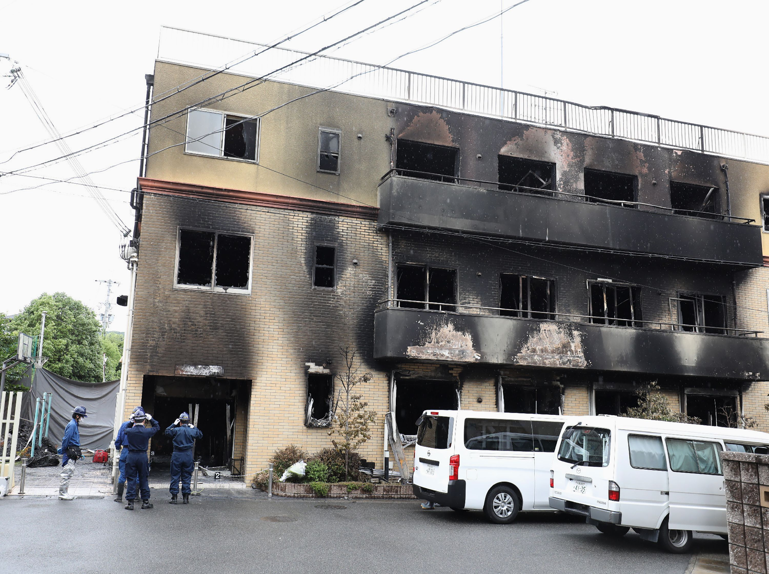 Japanese police officers inspect the scene where over 30 people died in a fire at the Kyoto Animation studio building in Kyoto on July 19, 2019 (Photo by JIJI PRESS/AFP/Getty Images)