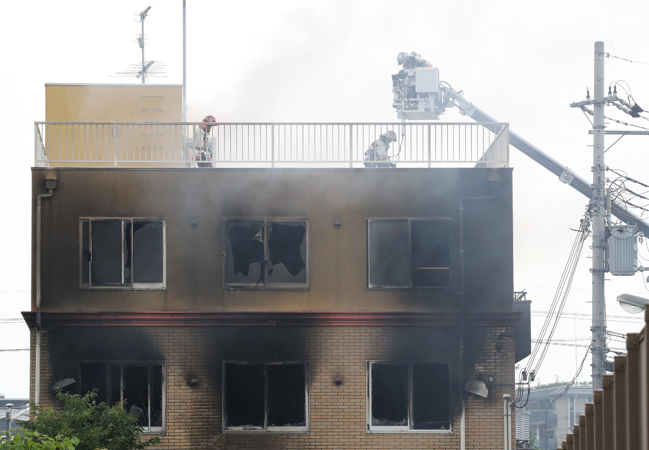 Firefighters and rescue personnel search an animation company building after a fire broke out in Kyoto on July 18, 2019. - At least 24 people are feared dead in a suspected arson attack on the animation company in the Japanese city of Kyoto on July 18, a fire department official told AFP. (Photo by JIJI PRESS/AFP/Getty Images)