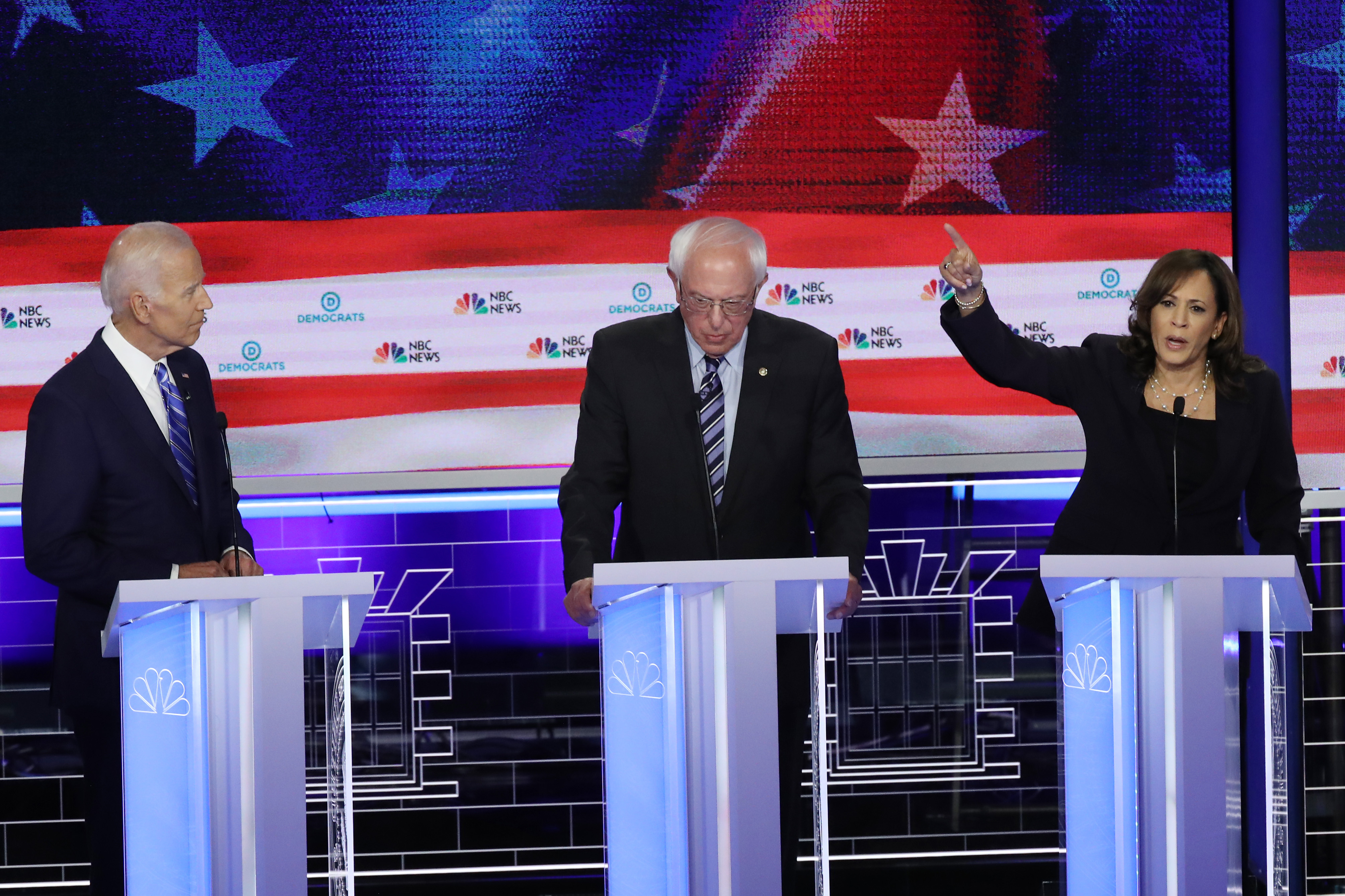 MIAMI, FLORIDA - JUNE 27: Sen. Kamala Harris (D-CA) speaks as Sen. Bernie Sanders (C) (I-VT) and former Vice President Joe Biden look on during the second night of the first Democratic presidential debate on June 27, 2019 in Miami, Florida. (Photo by Drew Angerer/Getty Images)